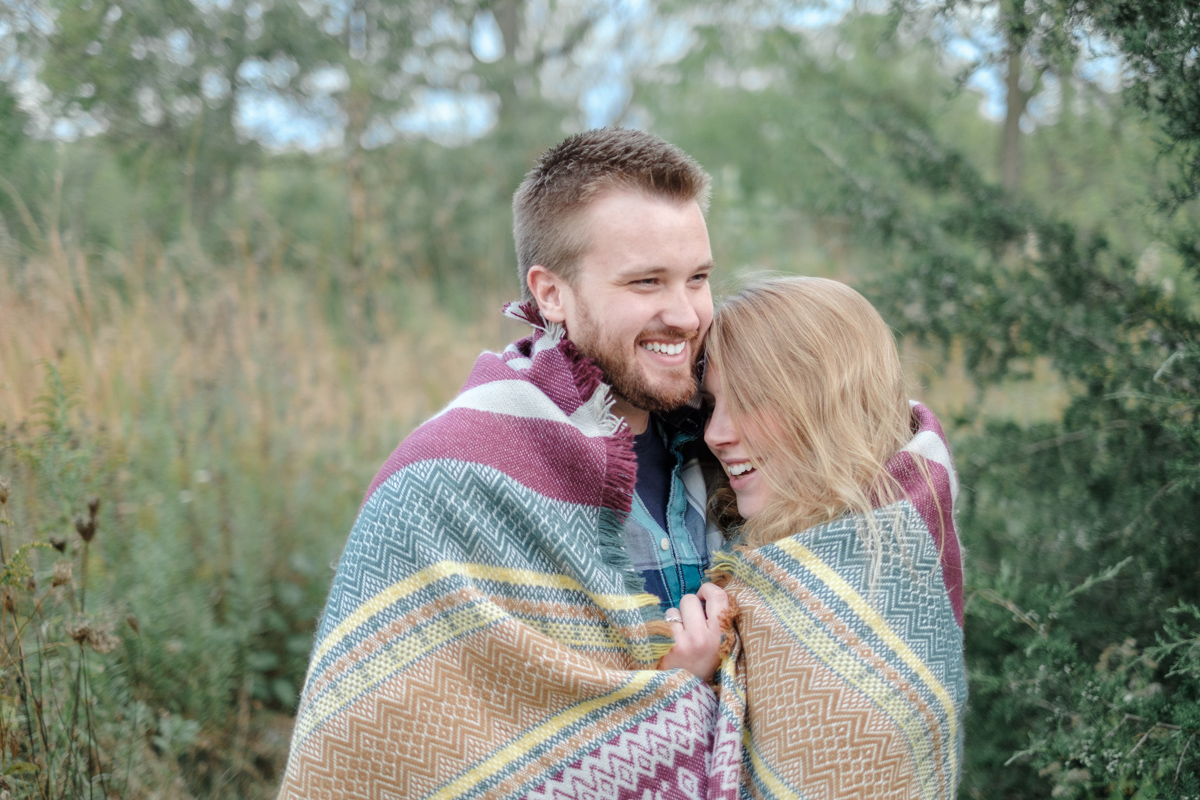 fall engagment portrait in macktown forest preserve with couple wrapped in blanket laughing