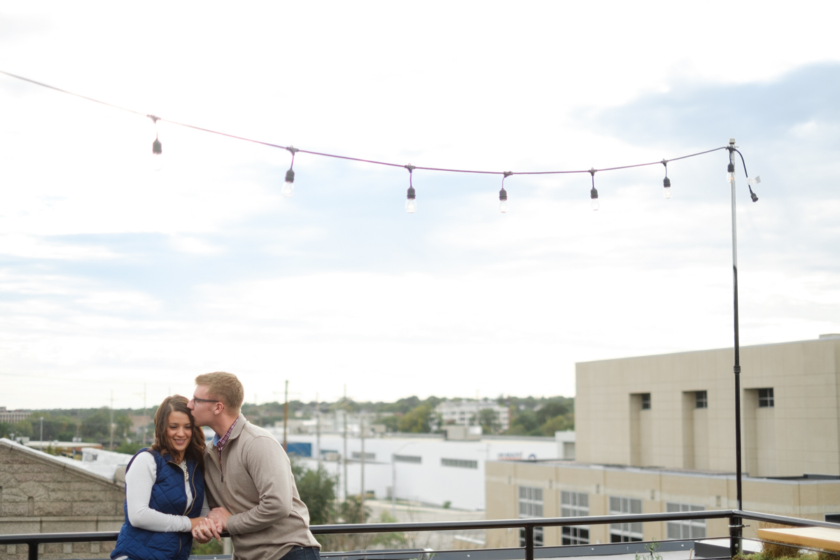 Engagement photo of Couple kissing under string lights at the rooftop bar of The standard on State in Rockford Illinois