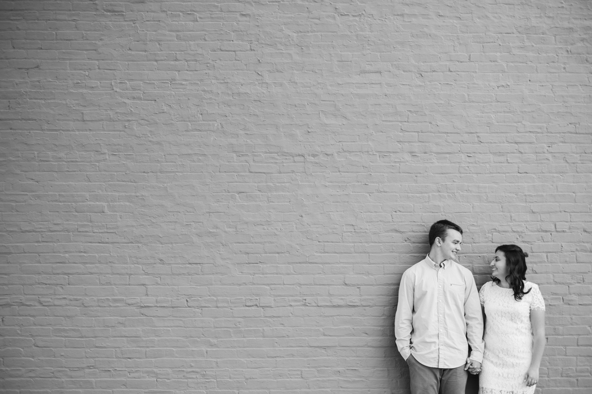 Engagement portrait of couple holding hands standing next to each other in front of painted brick wall in downtown rockton illinois