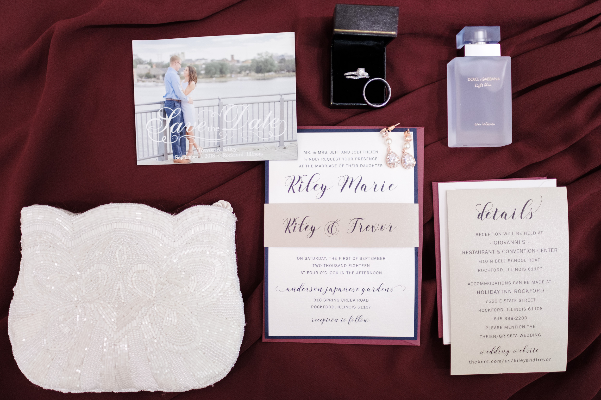 brides details, including rings, perfume, invitation suite and purse on maroon bridesmaid dress