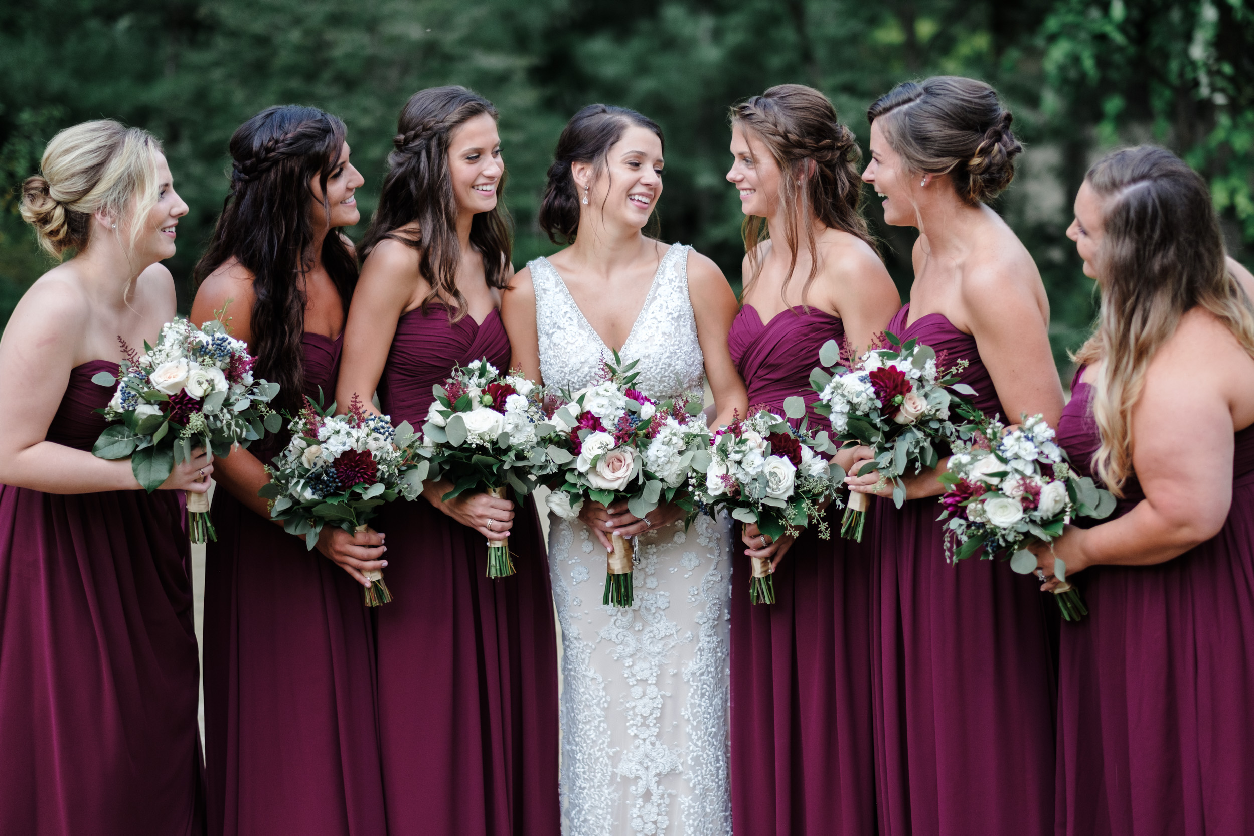 bride in white lace dress and brides maids in maroon dresses holding flowers while talking and laughing with eachother