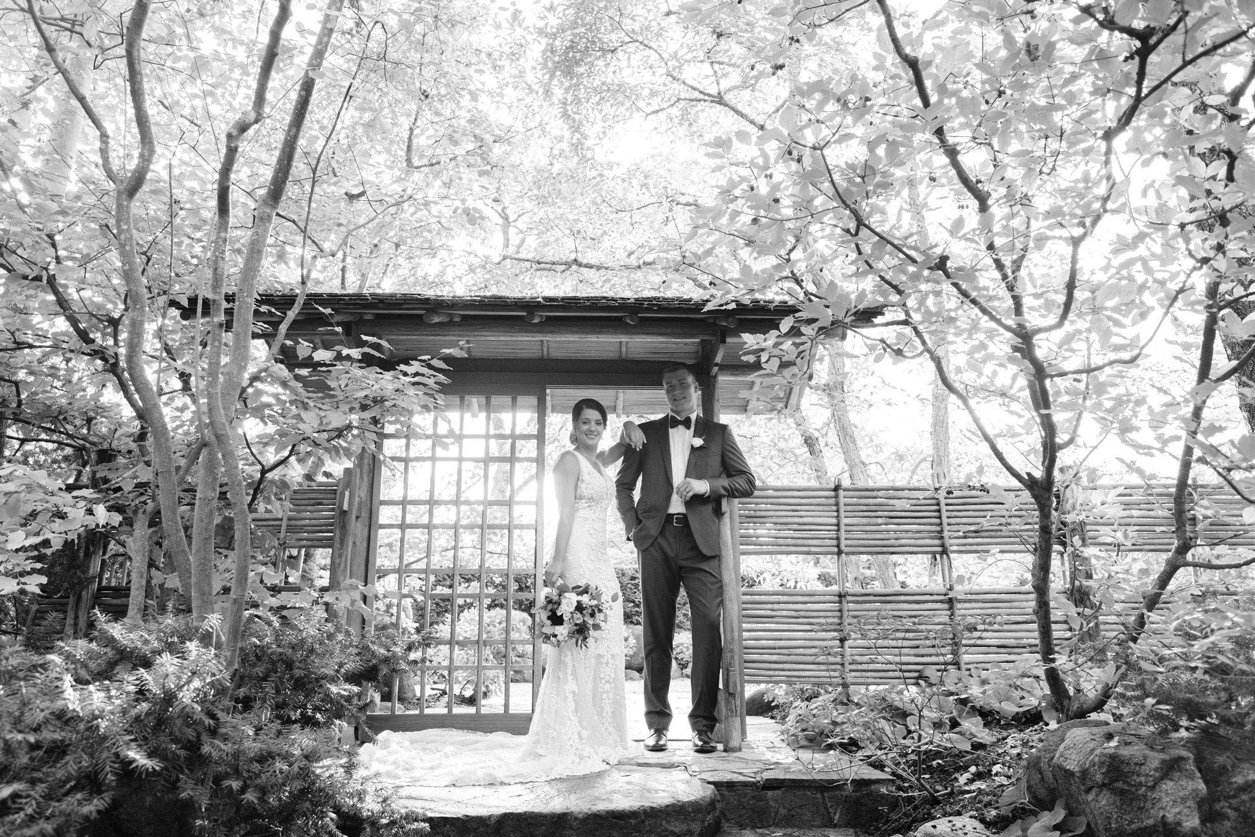 black and white photo of bride and groom with sun behind them under Japanese archway