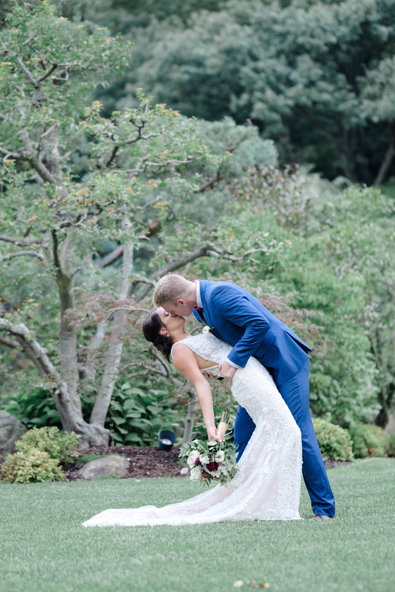 Groom in blue suit dips his bride in Anderson Japanese Gardens
