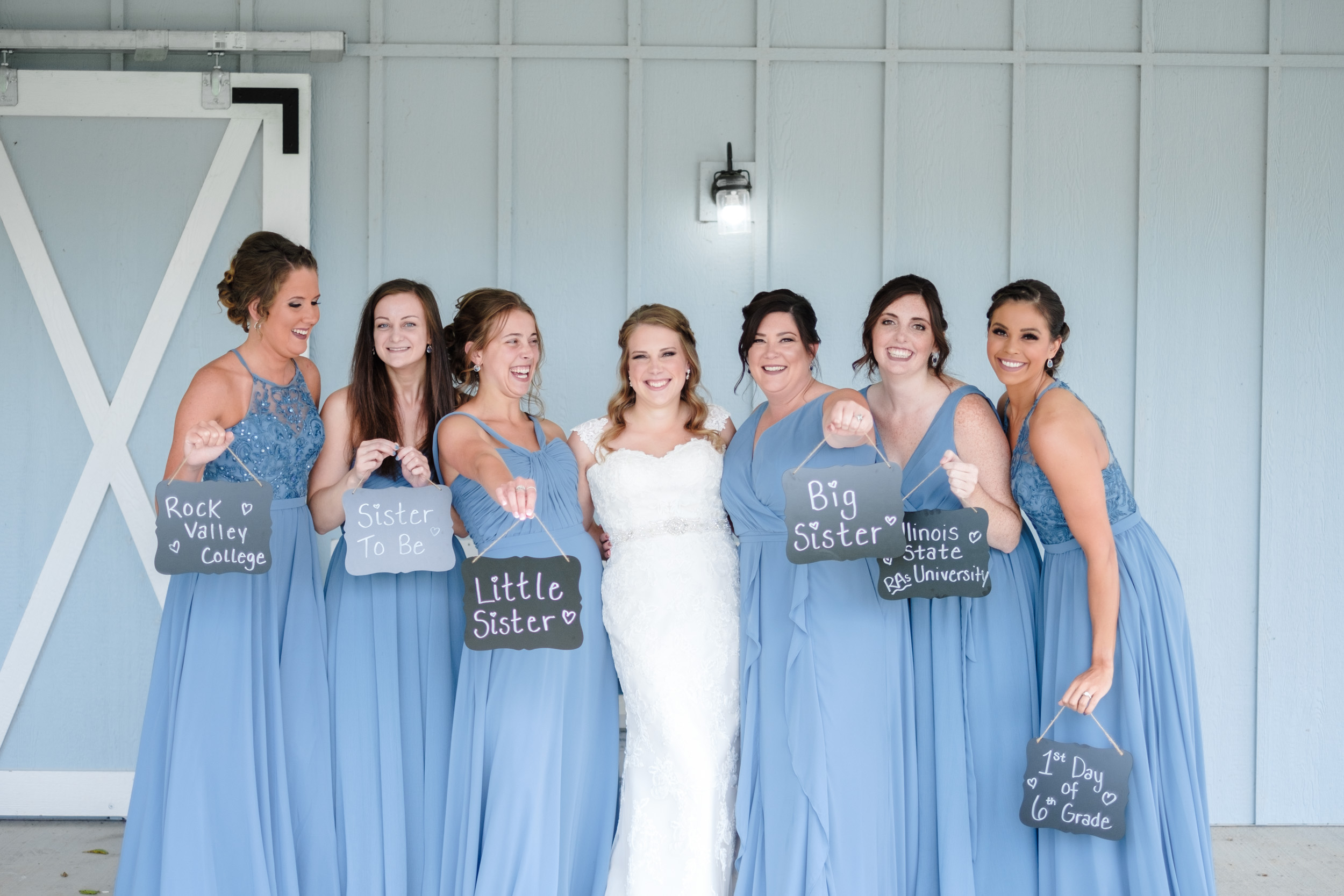 Bridesmaids in blue dresses in front of reception barn holding signs of how they met before wedding at the fields reserve