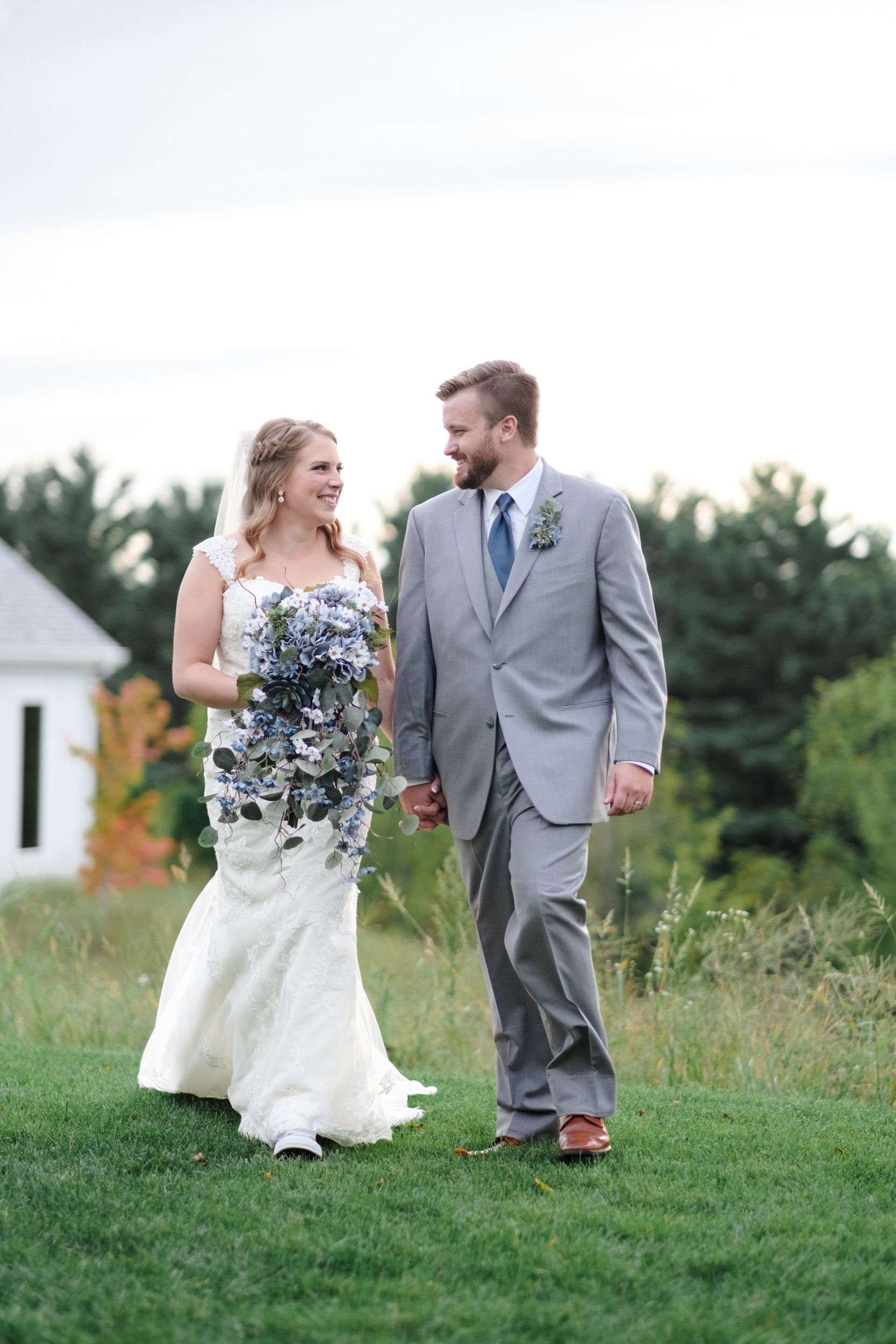 Couple holds hands and joyfully runs smiling and laughing at The Fields Reserve in Stoughton on their wedding day