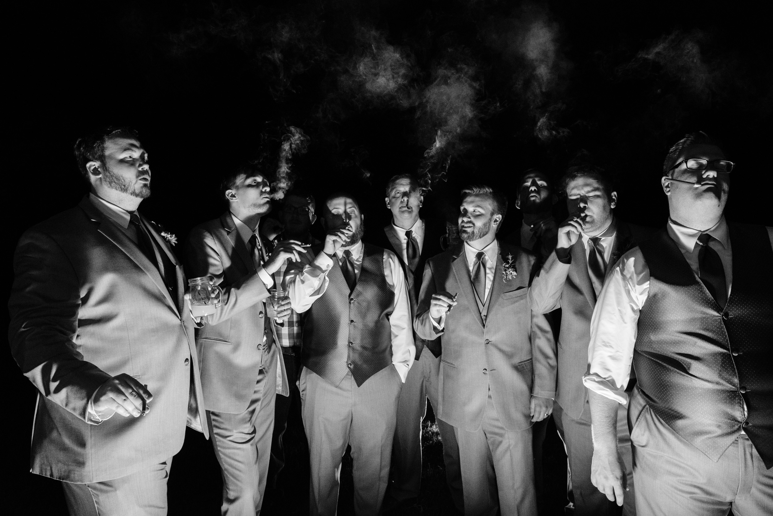 black and white photography with groomsmen and groom smoking cigars at the reception