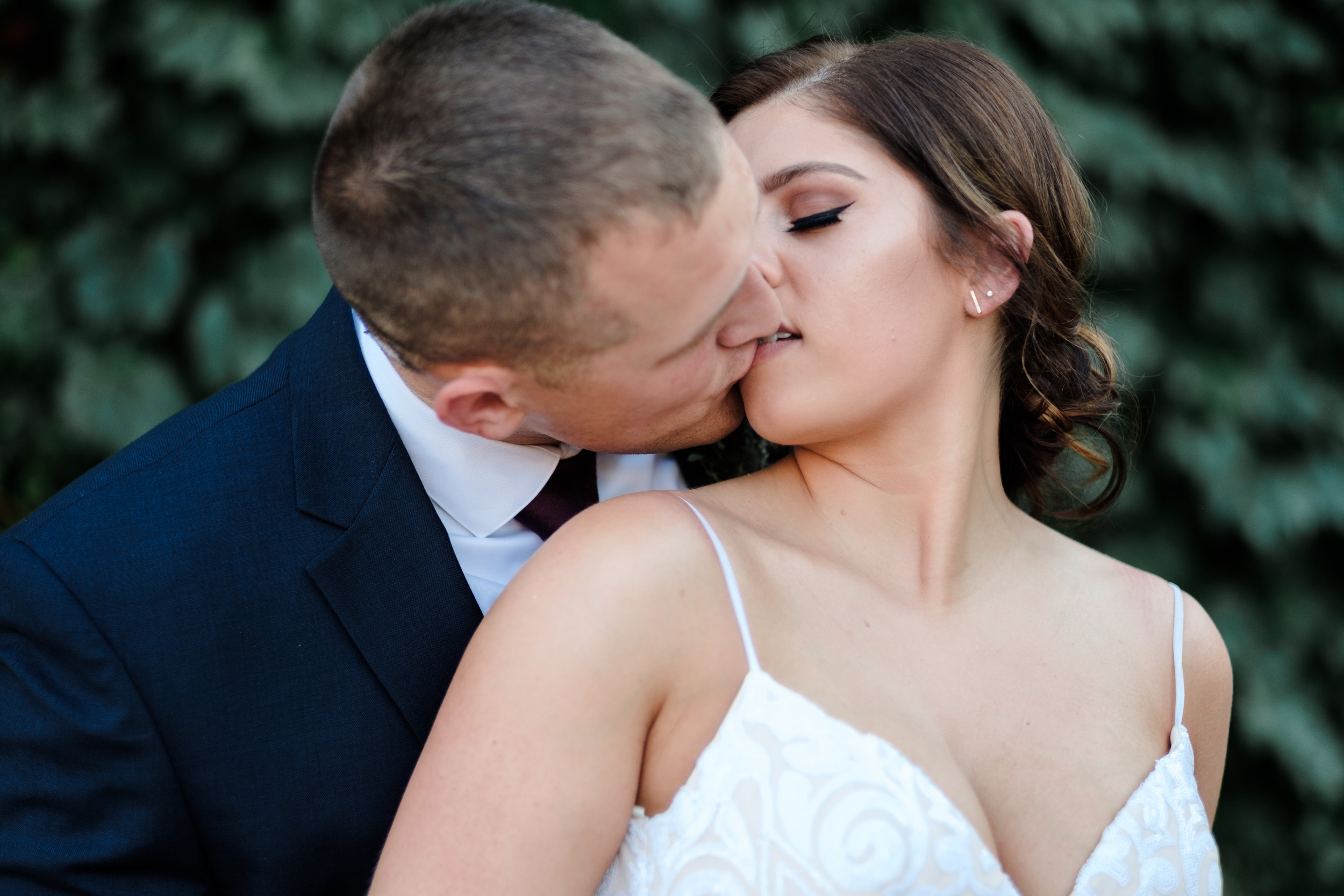 Bride and groom kissing in alley behind the wagner house in freeport with ivy on the brick walls behind them