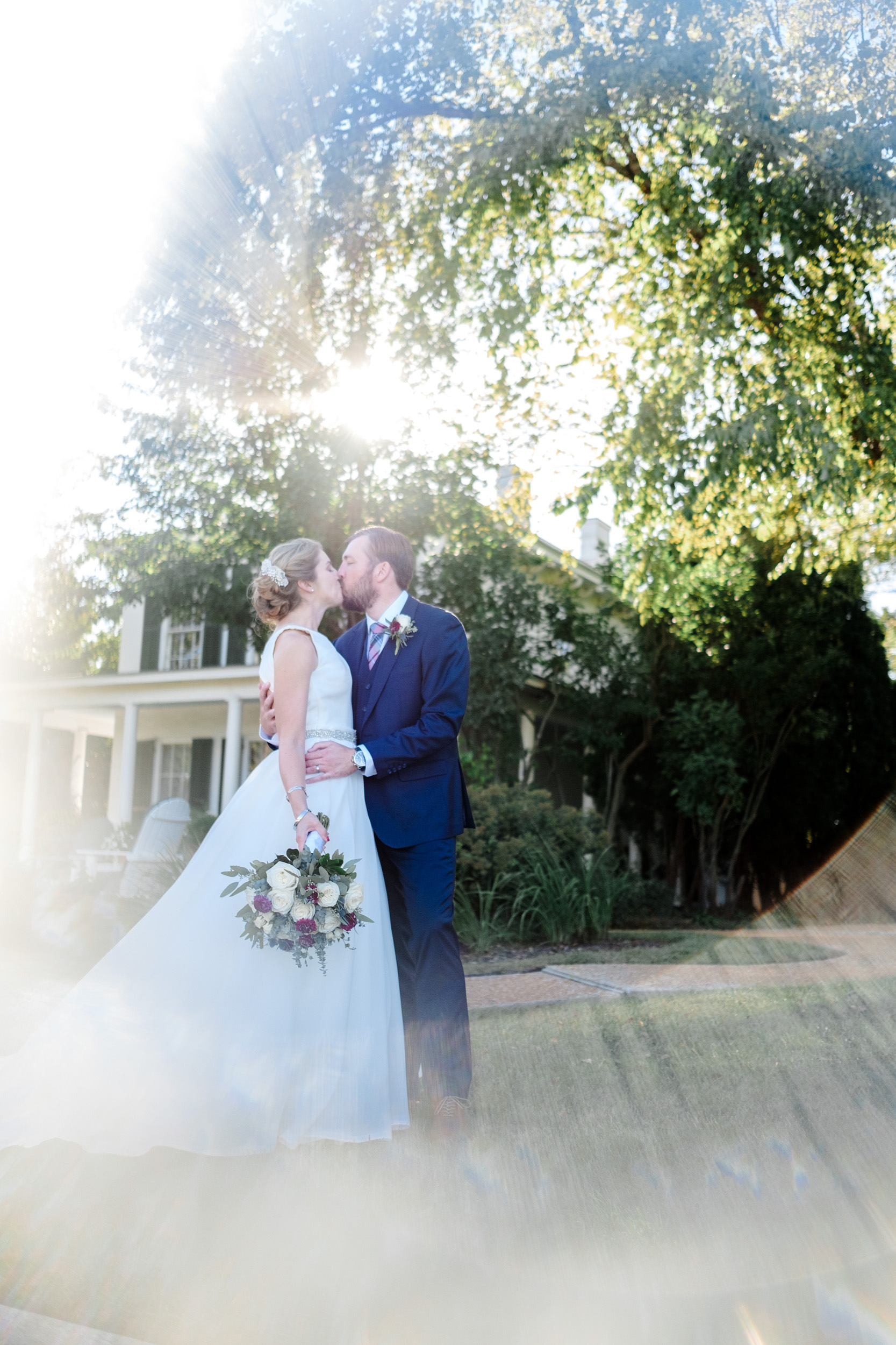Bride and groom kiss with historic home in Galena behind them with sun setting and artistic light flare frames them.