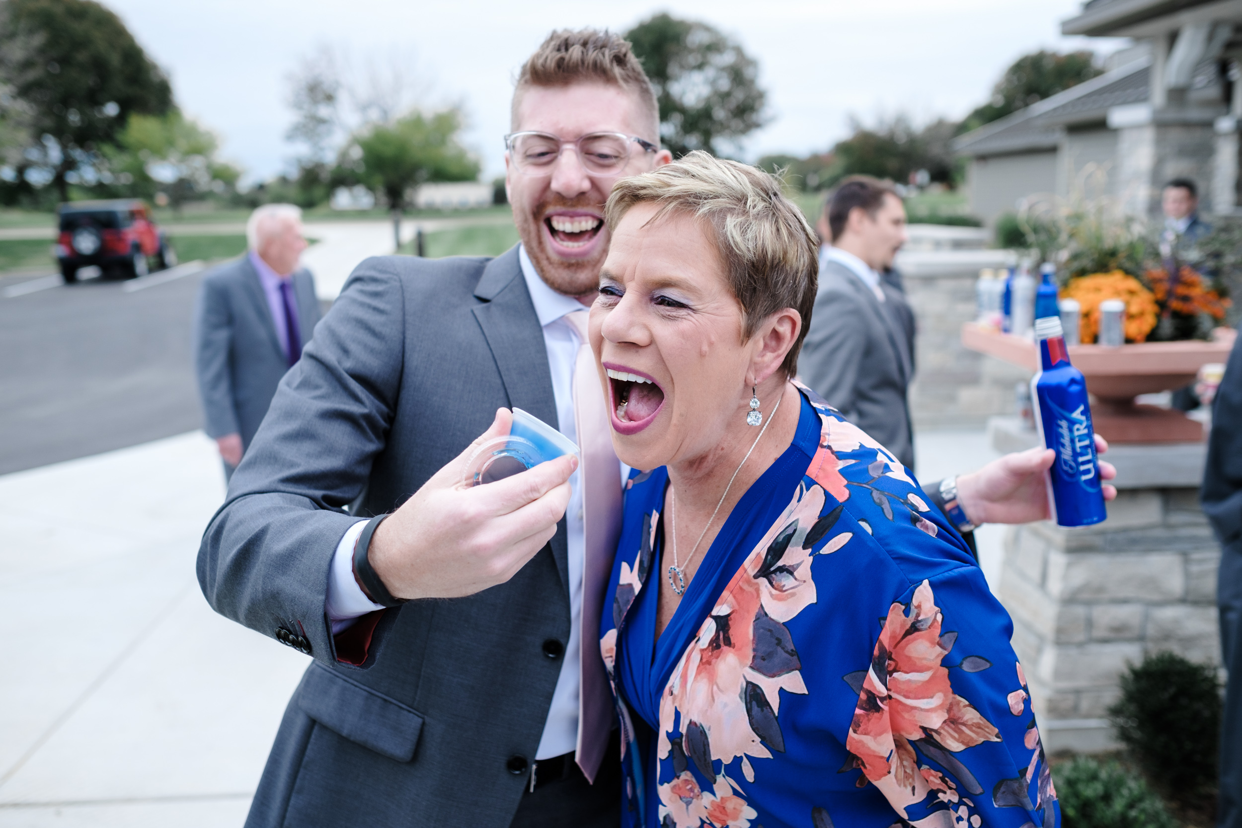 Candid photo of groom mom doing jello shot at Rockford Bank and Trust Pavilion.