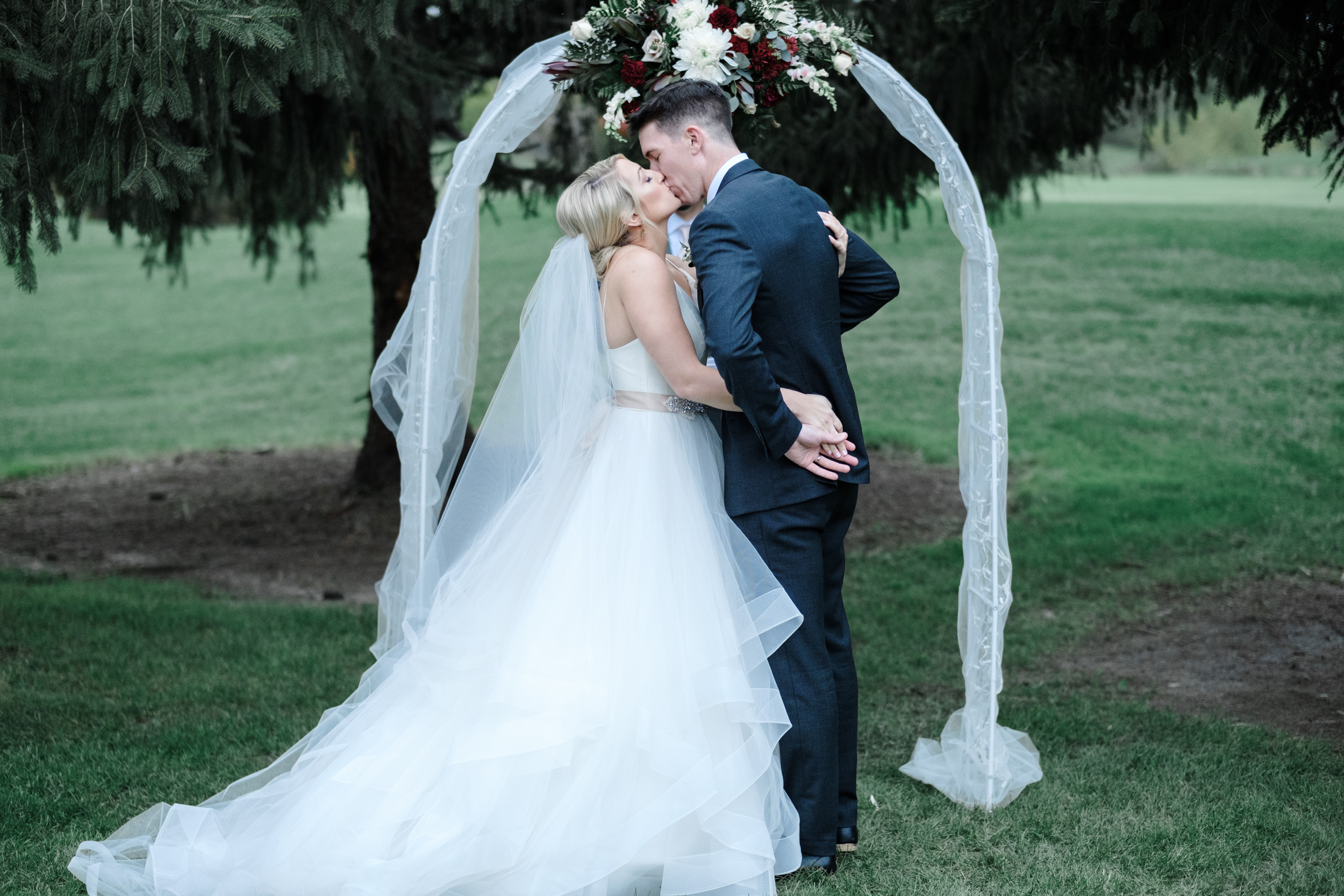 Bride and groom first kiss at outdoor ceremony at Rockford Bank and Trust Pavilion.