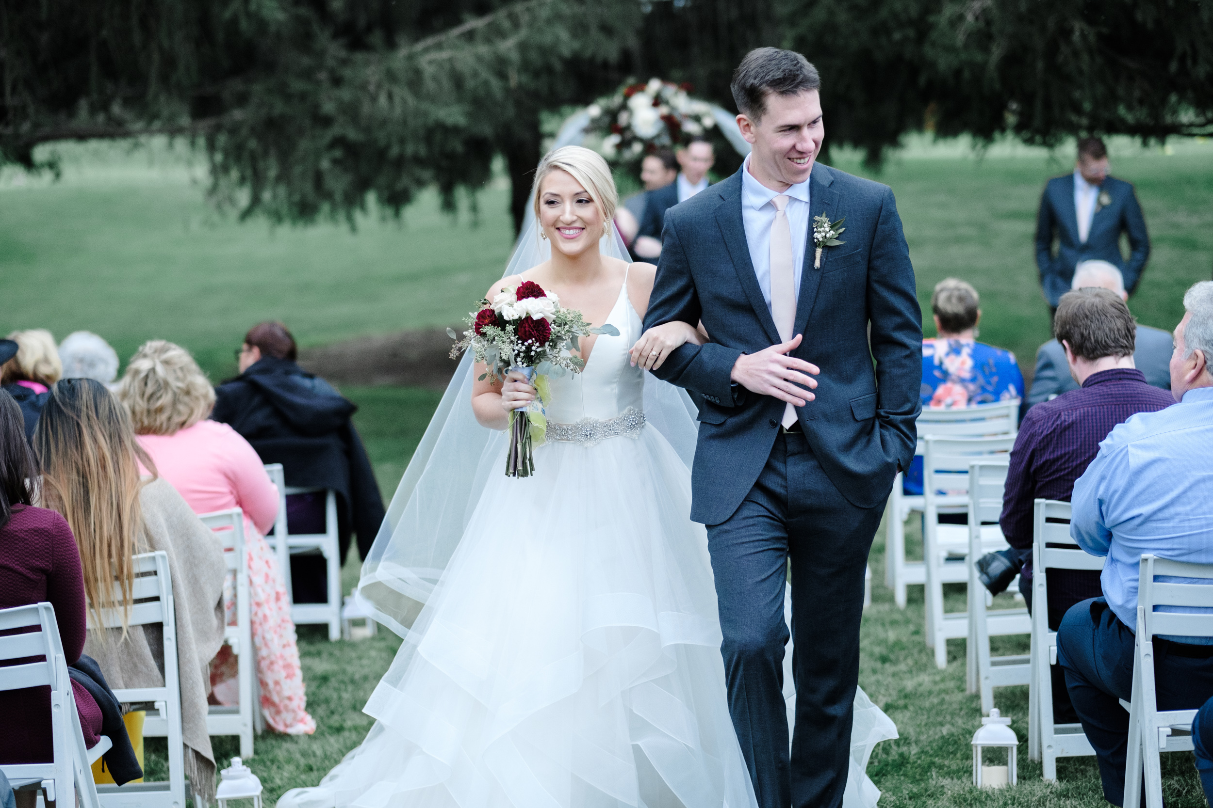 Bride and groom beaming as they walk out of their outdoor ceremony at Rockford Bank and Trust Pavilion.