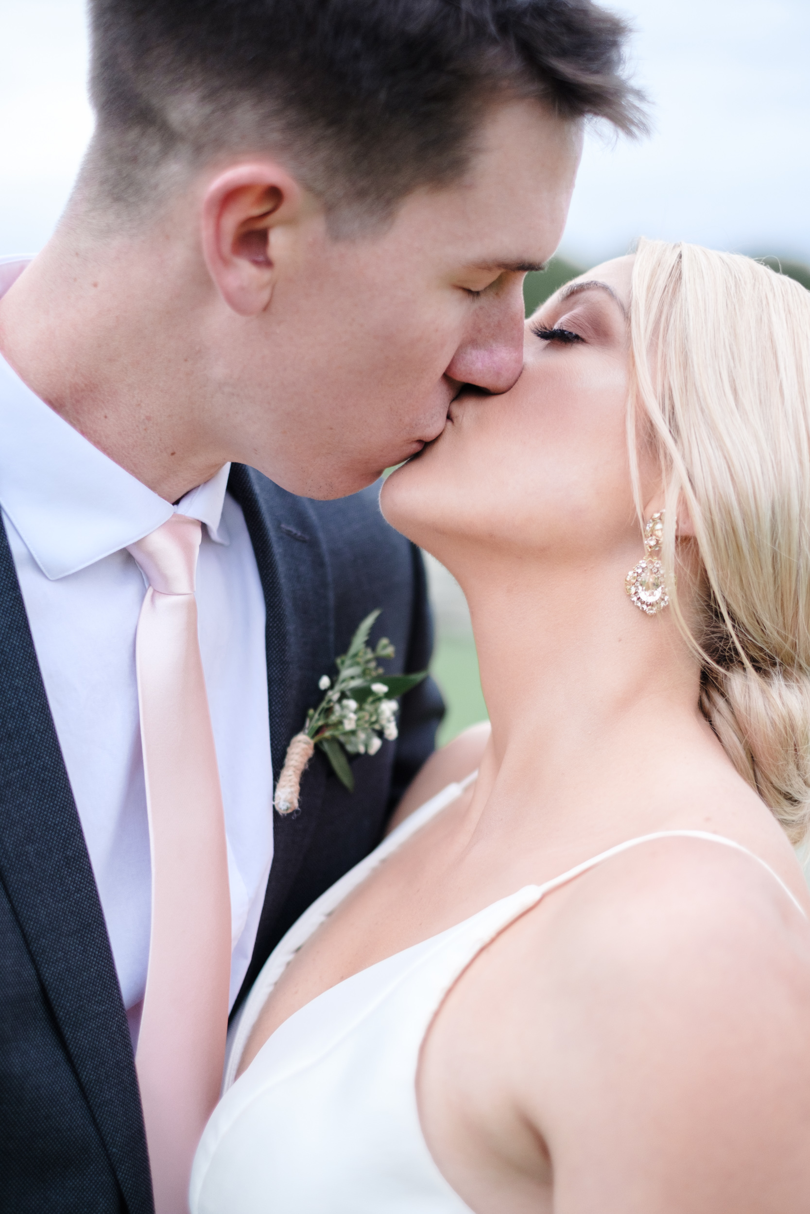 Beautiful blonde bride kissing groom in grey suit on golf course at summer wedding at Rockford Bank and Trust Pavilion.
