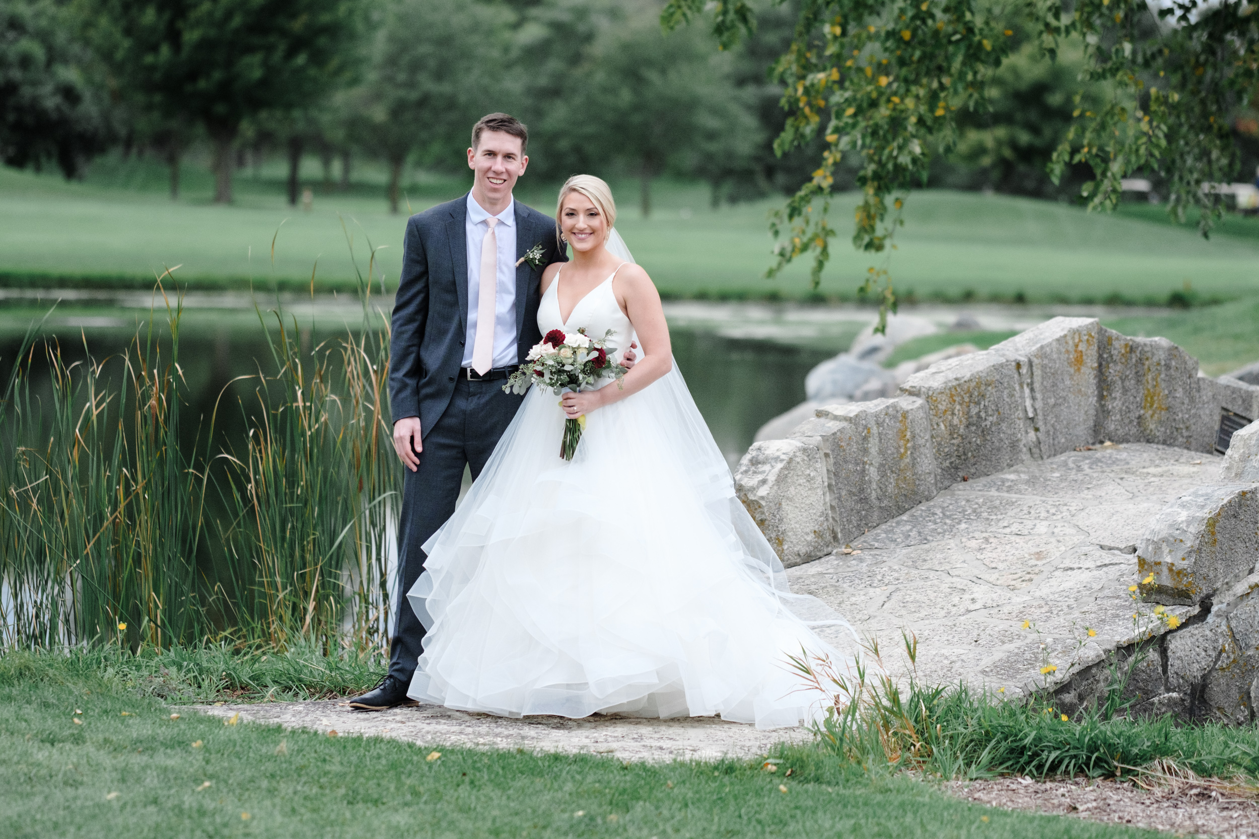 Bride and groom on stone bridge at Rockford Bank and Trust Pavilion.