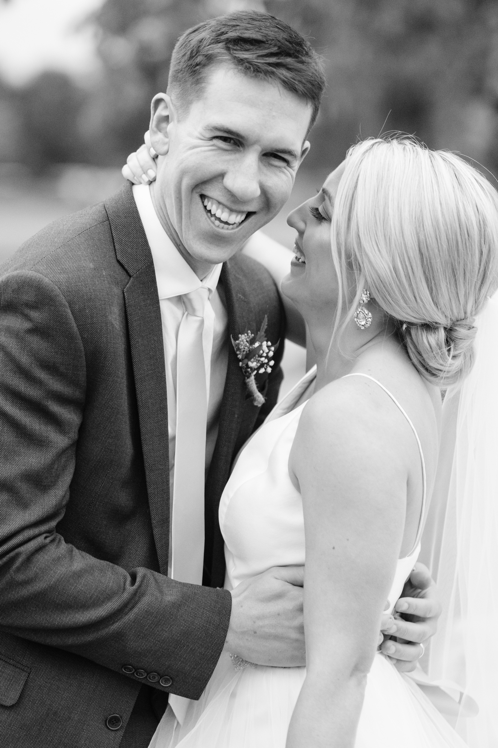 Black and white image of couple embracing and laughing during their wedding at Aldeen golf course at The Rockford Bank and Trust Pavilion.