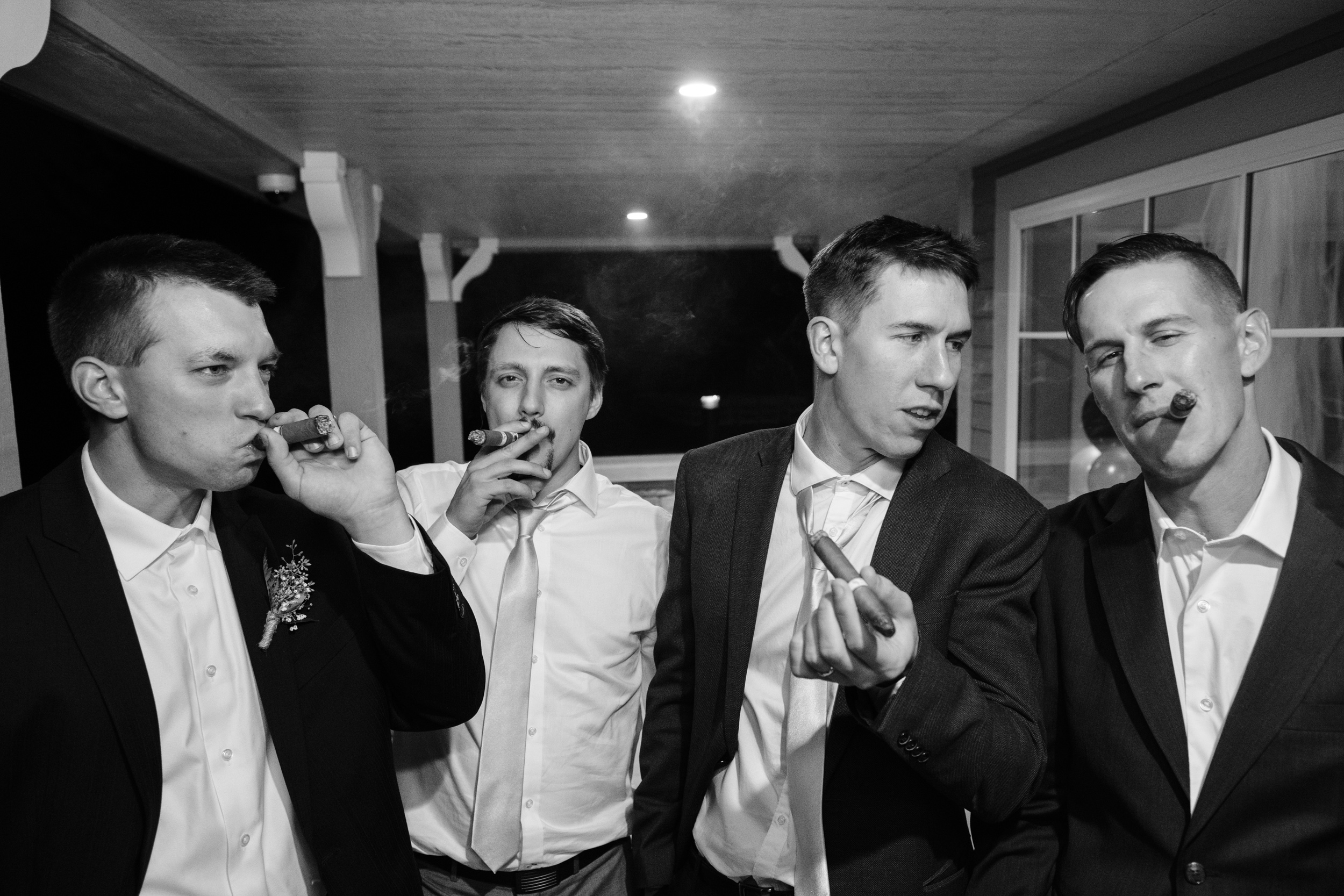 classic blank and white photography with the groom and groomsmen smoking cigars at the reception in Rockford, IL