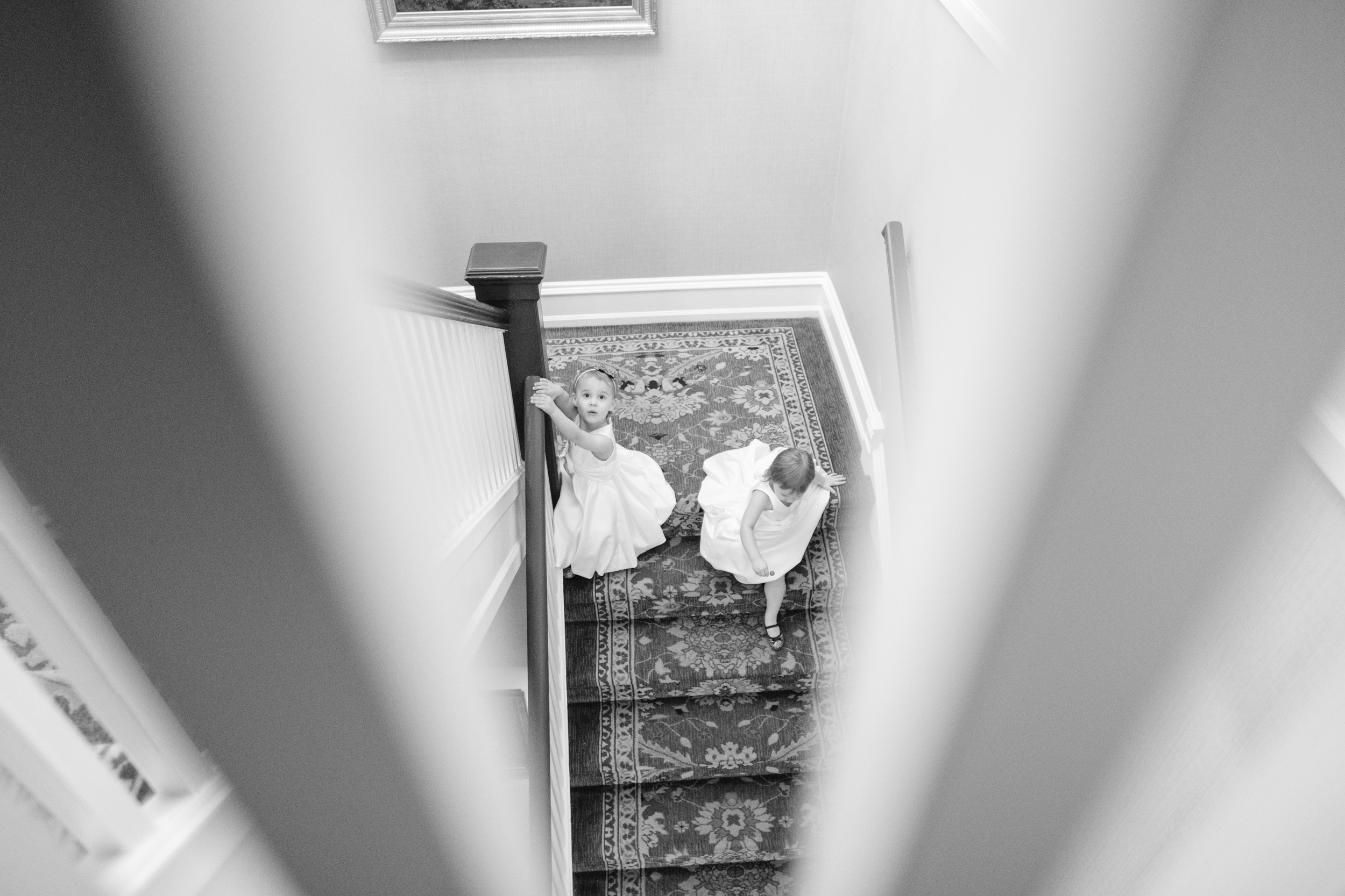 young flower girls play on stairs at cog hill golf and country club before wedding