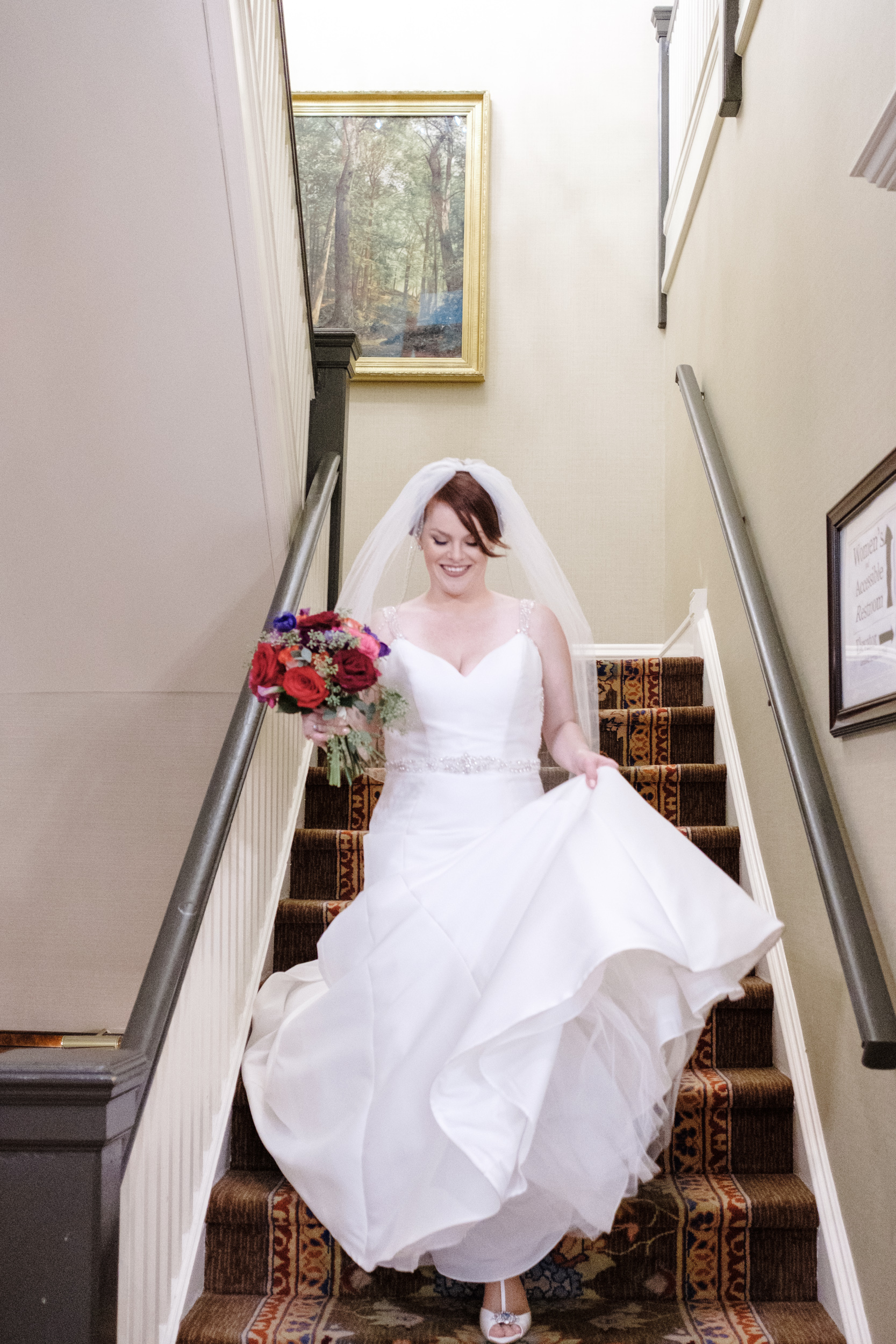Bride walking down stairs to her wedding at cog hill