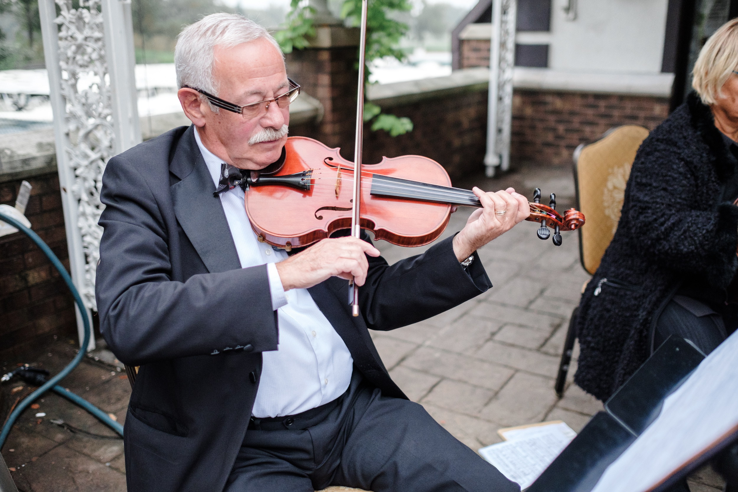 violinist playing before start of outdoor wedding at cog hill