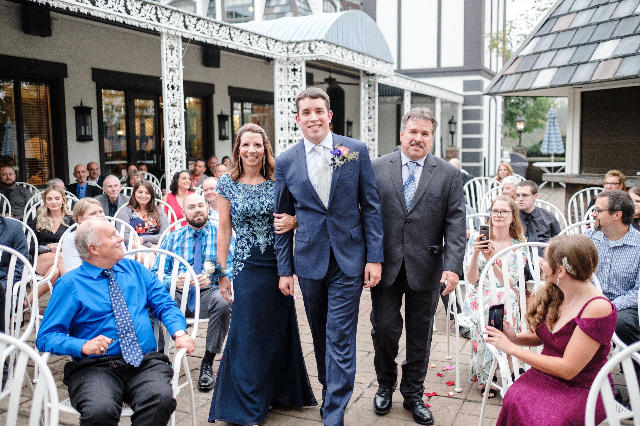 Groom in blue suit escorting parents down the aisle before outdoor fall wedding