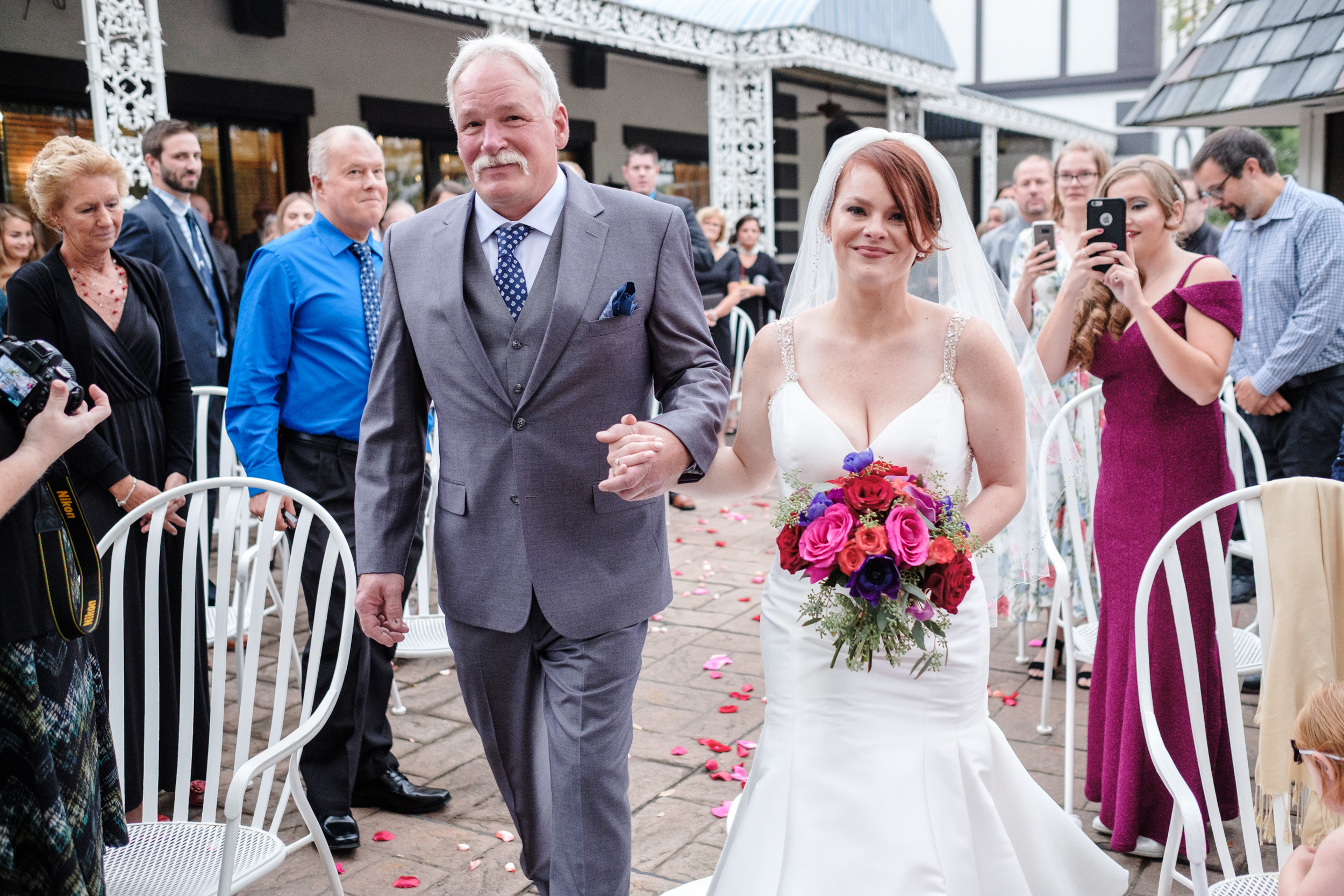 bride in white dress with colorful flower walking down aisle to be married