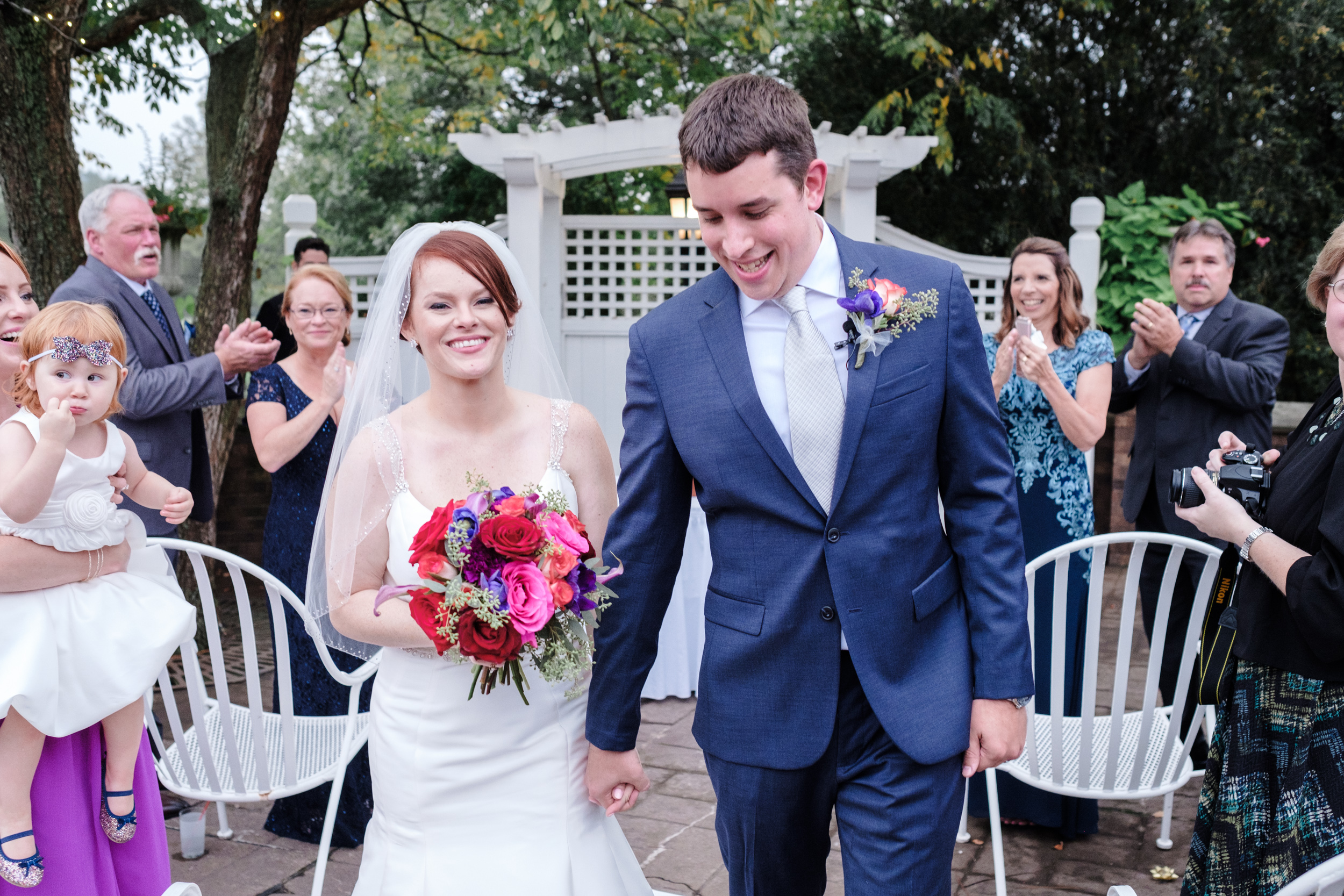 bride and groom holding hands smiling walking out of wedding ceremony