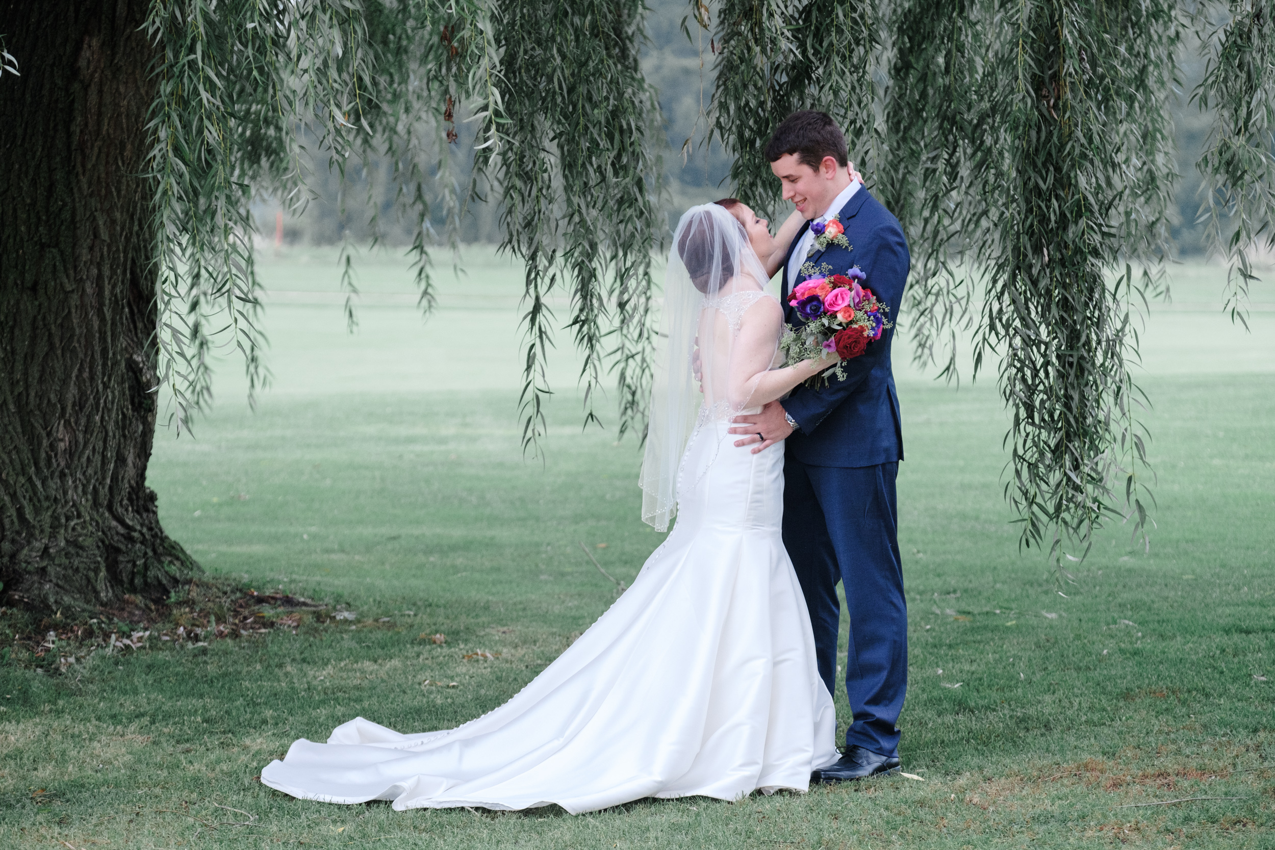 bride and groom embrace under willow tree on cog hill golf course for portraits