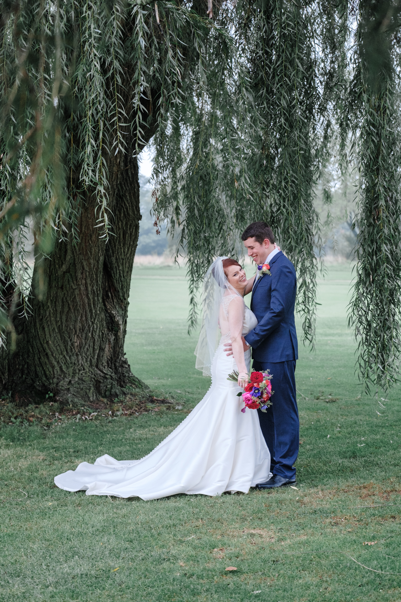 bride and groom kiss under willow tree on cog hill golf course for portraits