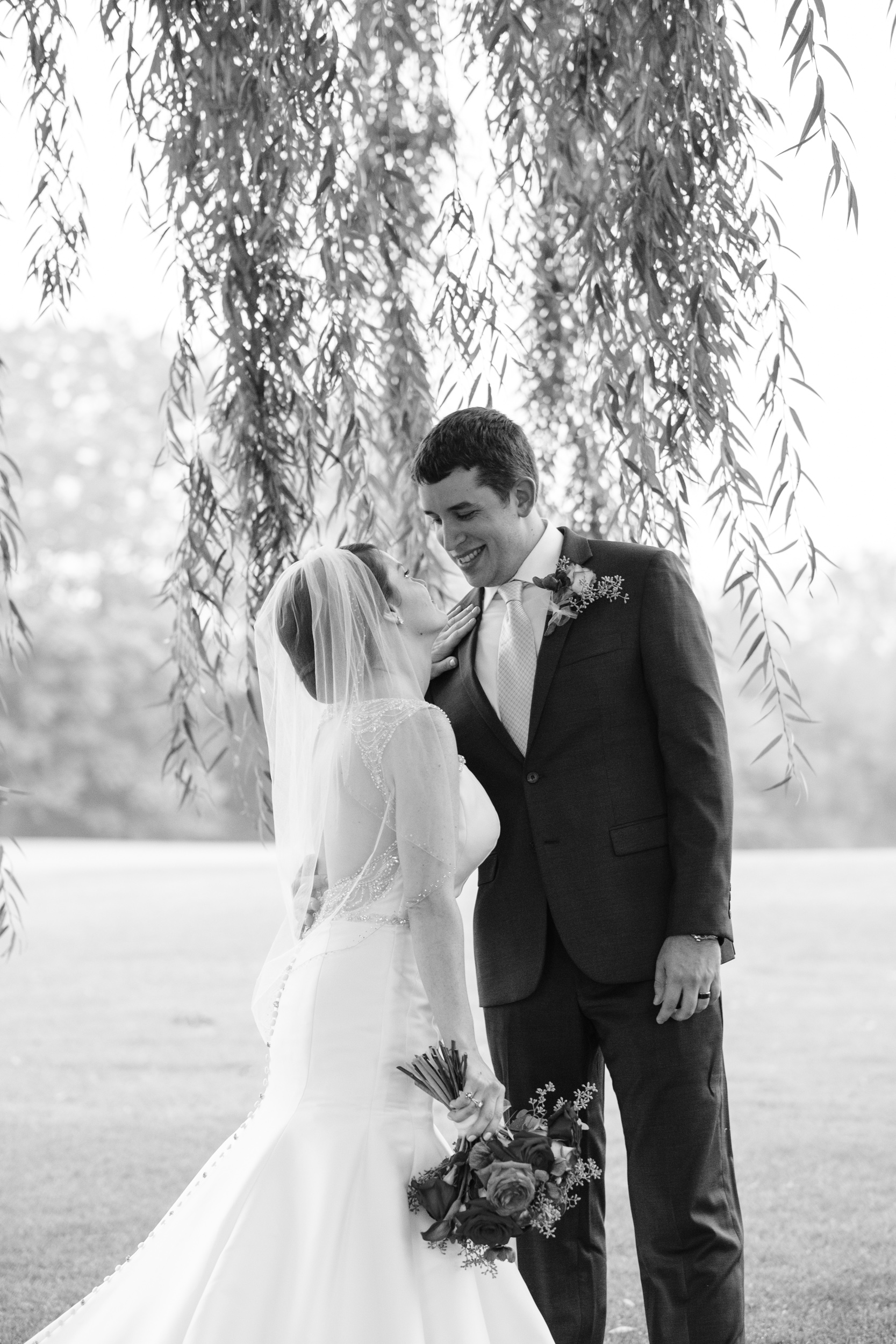 bride and groom laugh under willow tree on cog hill golf course for candid portraits