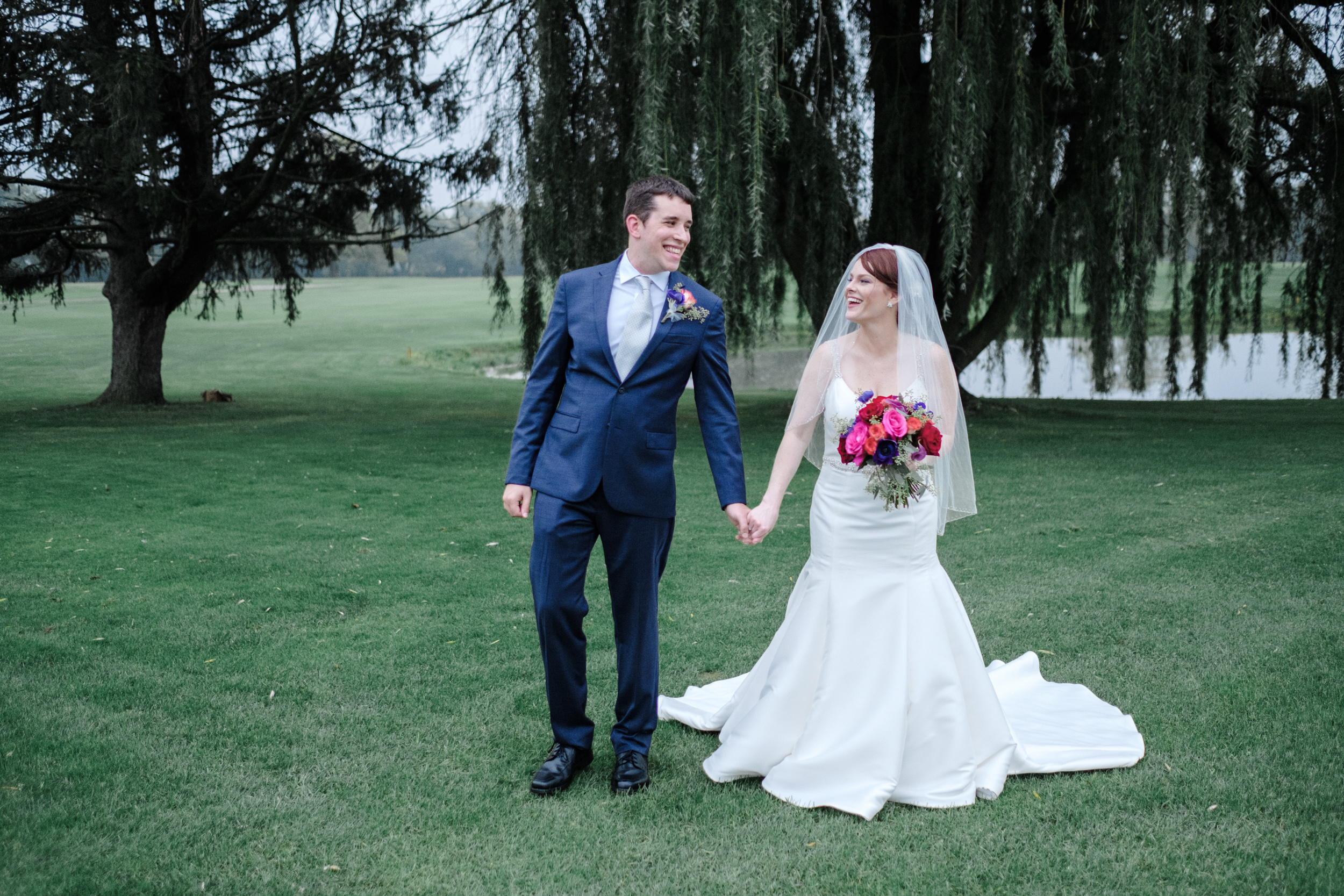 couple naturally walking on golf course for candid fun wedding portrait by best rockford wedding photographer
