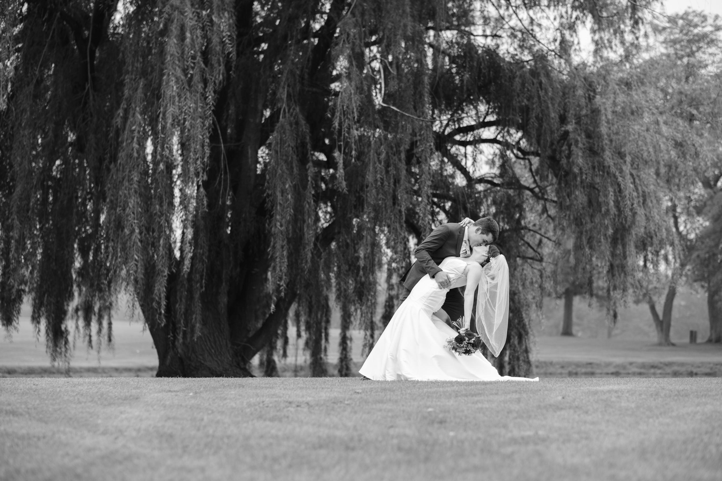 black and white groom dipping bride elegant wedding photo