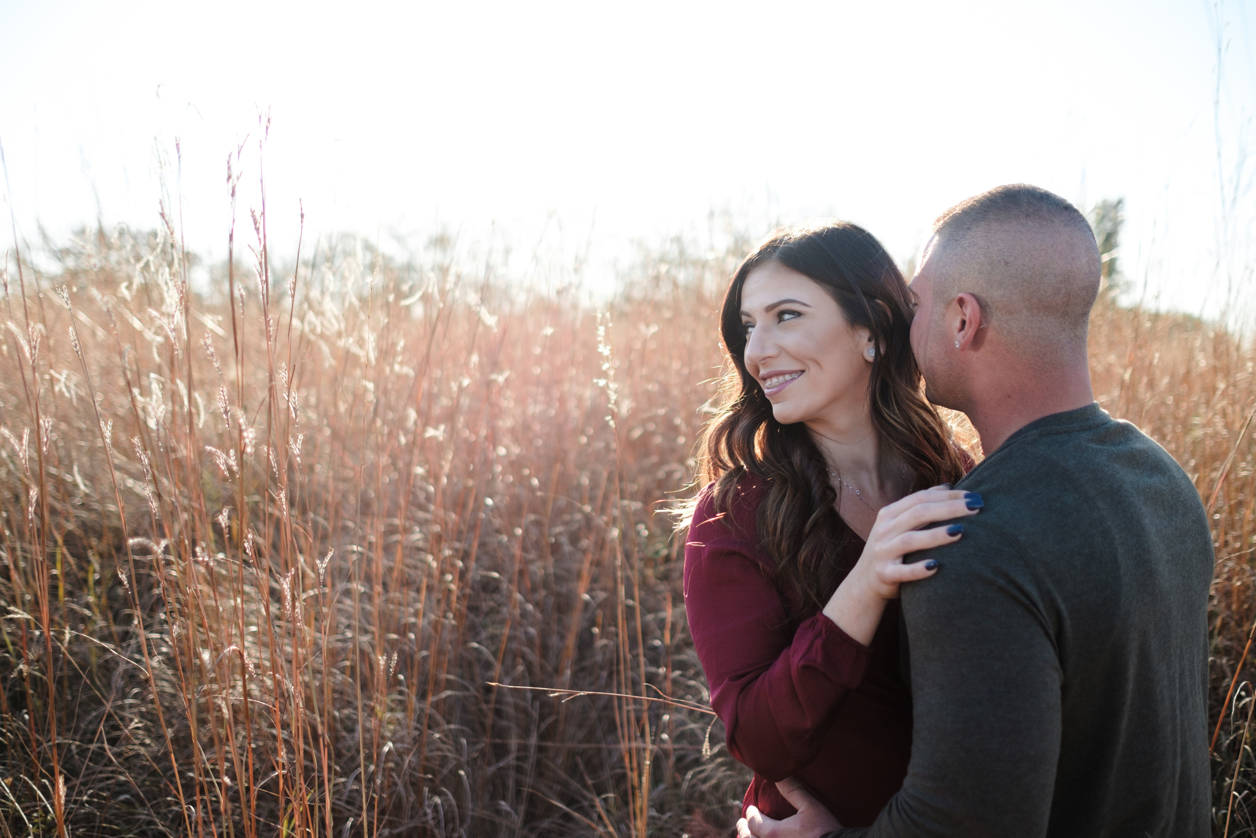 Bride with beautiful long dark hair looks away from groom with tall grass field behind them and the sun setting during golden hour in Rockford, Illinois.