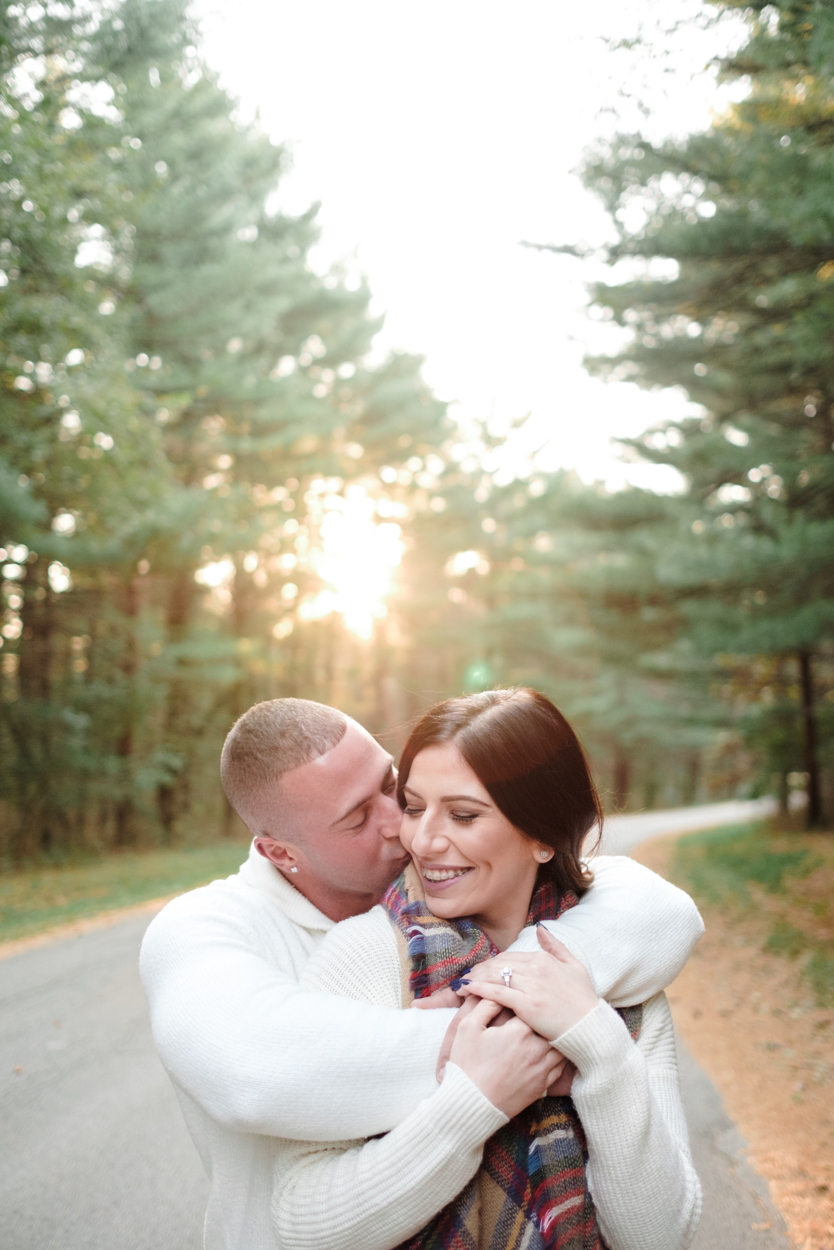 Couple embrace and kiss as sun sets behind them into the pine trees at Rock Cut state park in Rockford, Illinois.
