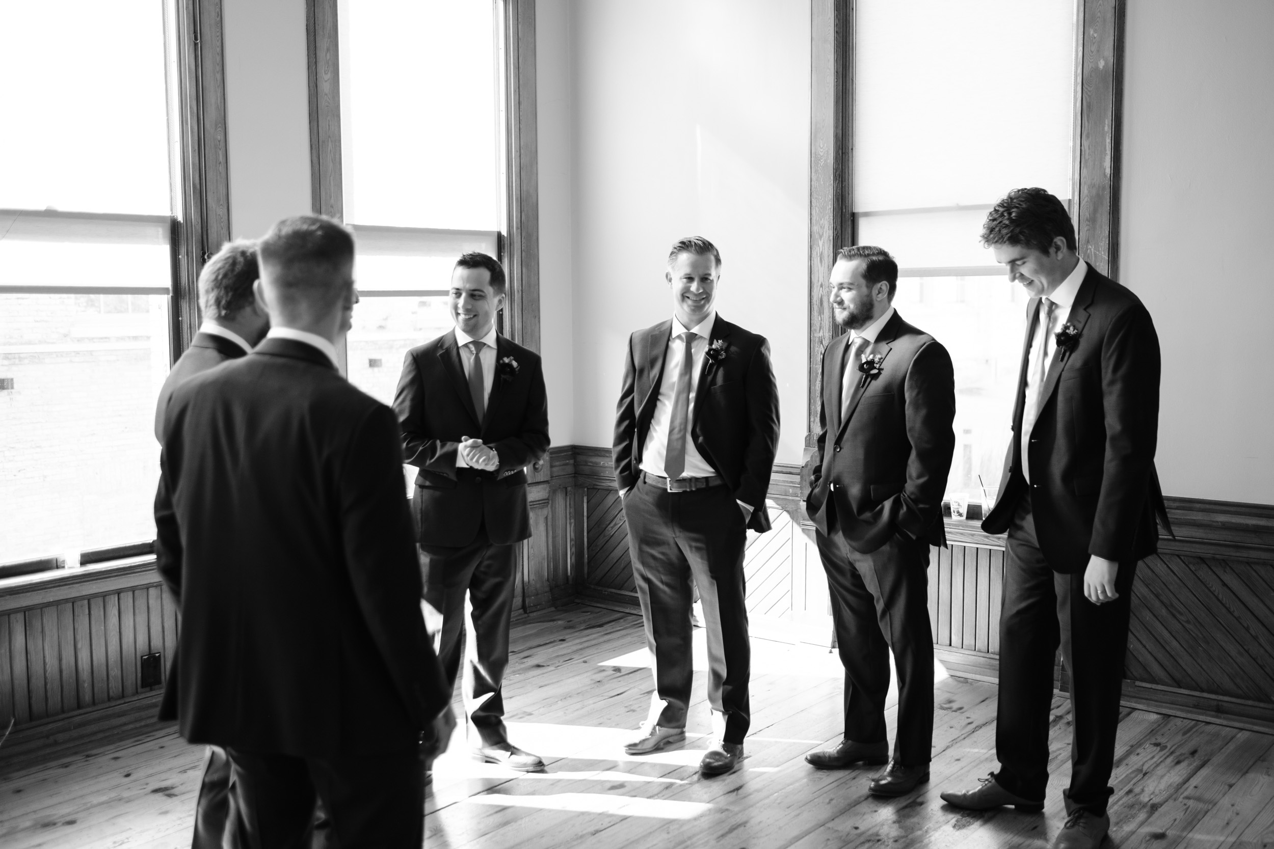 Groom and groomsman candid relaxing before ceremony by rockford wedding photographer b. adams photography at Pabst best place.