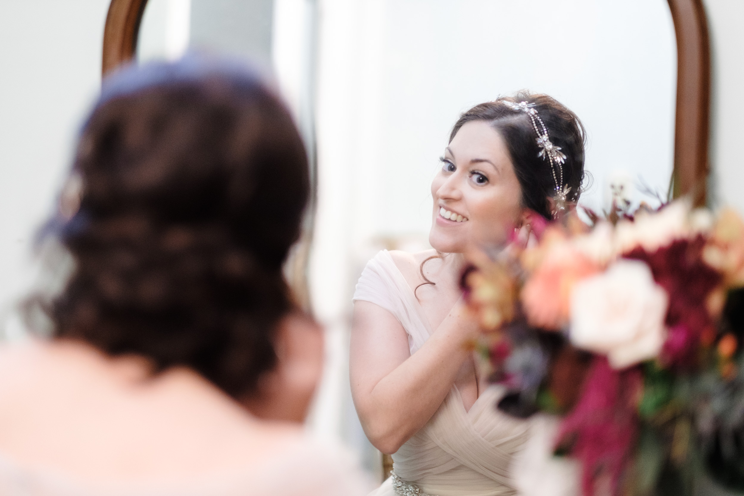 Bride putting diamond earrings on with maroon and orange flowers  with braided hair by rockford wedding photographer b. adams photography