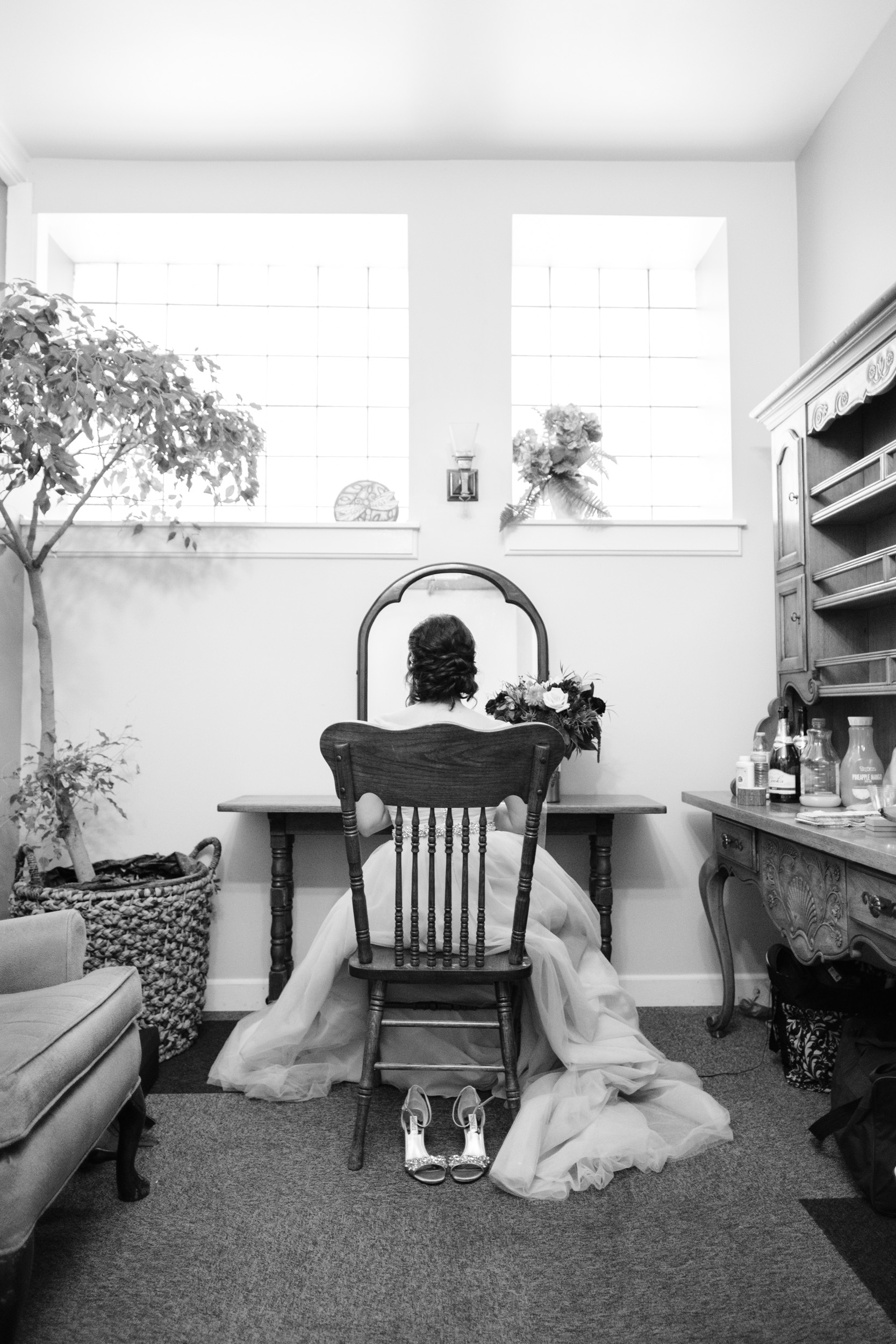 Bride getting ready in rocking chair at Pabst BEst place by rockford wedding photographer b. adams photography