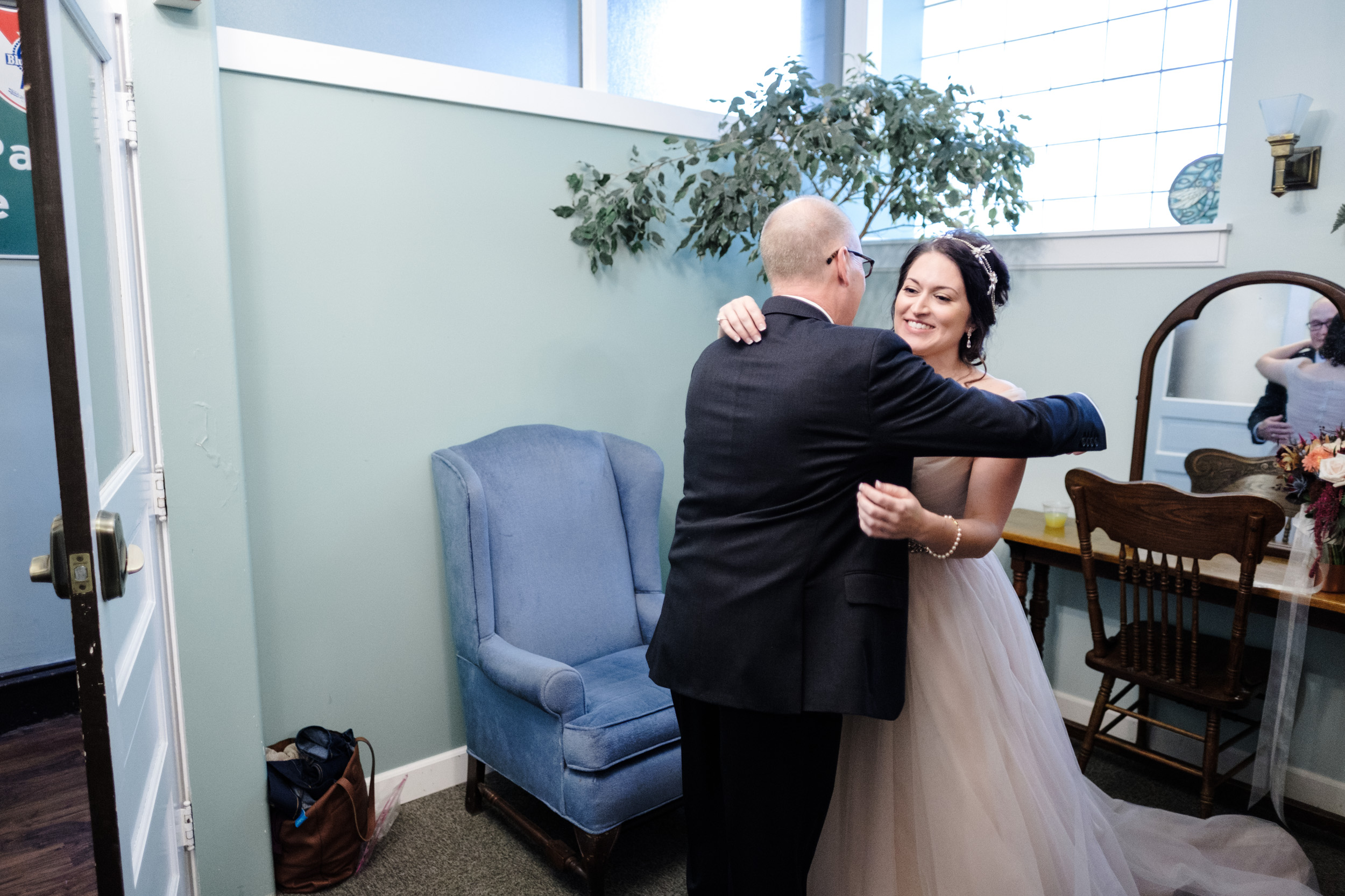 Bride and father embrace and cry as he has his first look with his daughter at pabst best place, milwaukee wisconsin. by rockford wedding photographer b. adams photography