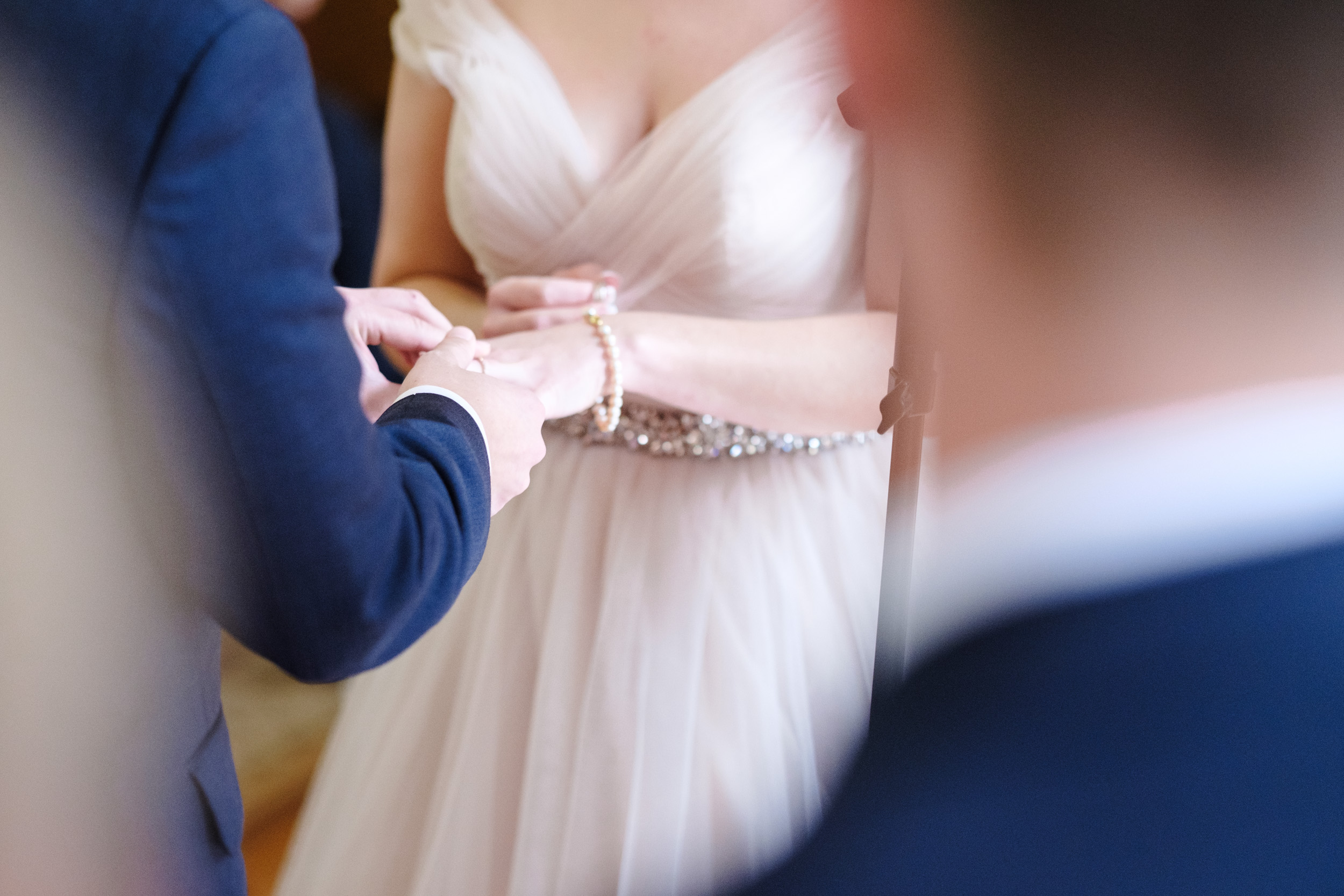 groom in blue suit slips rose gold wedding band onto brides hand