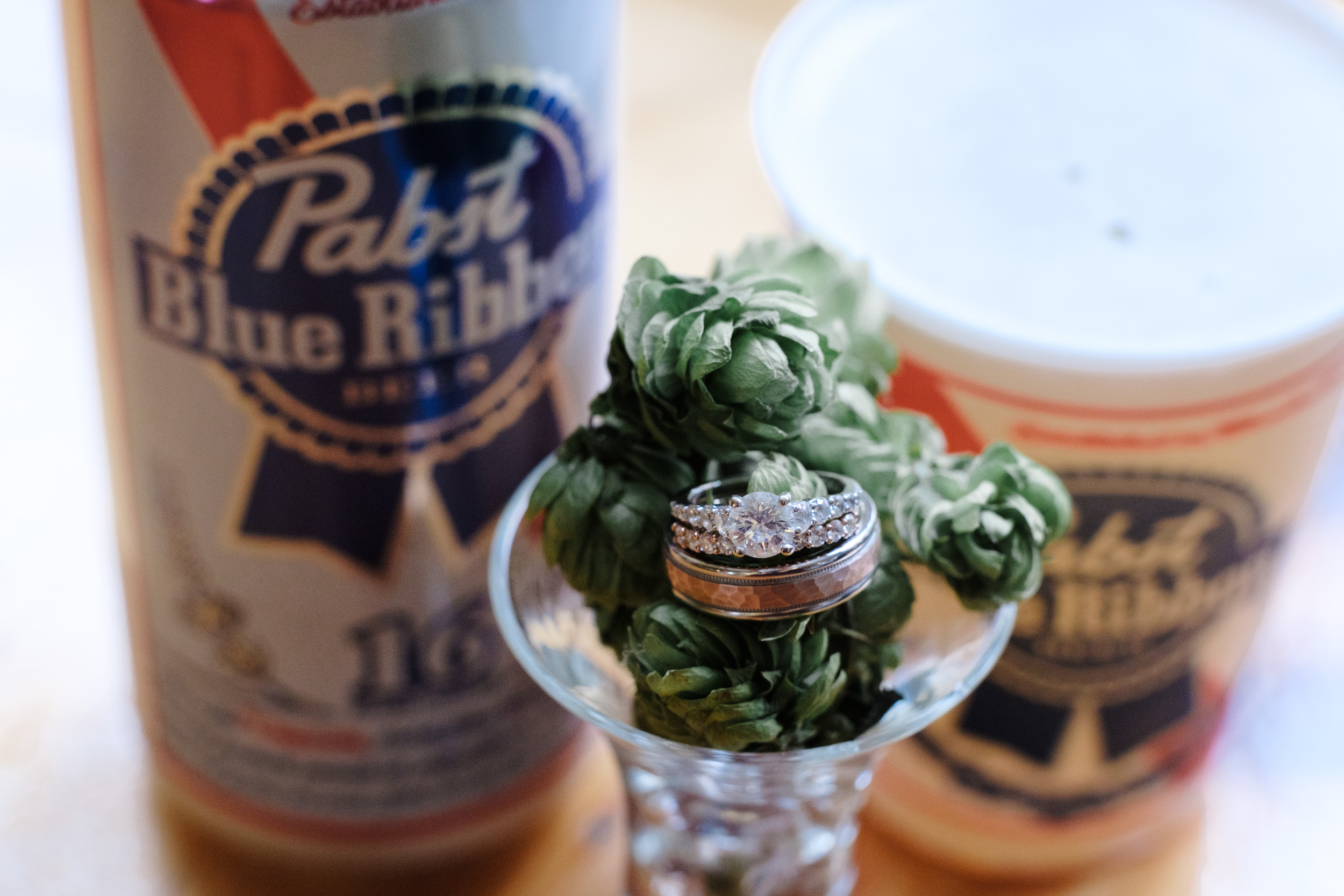 Beautiful rose gold wedding ring and bands resting on fresh hobs at Milwaukees, Pabst Best Place.