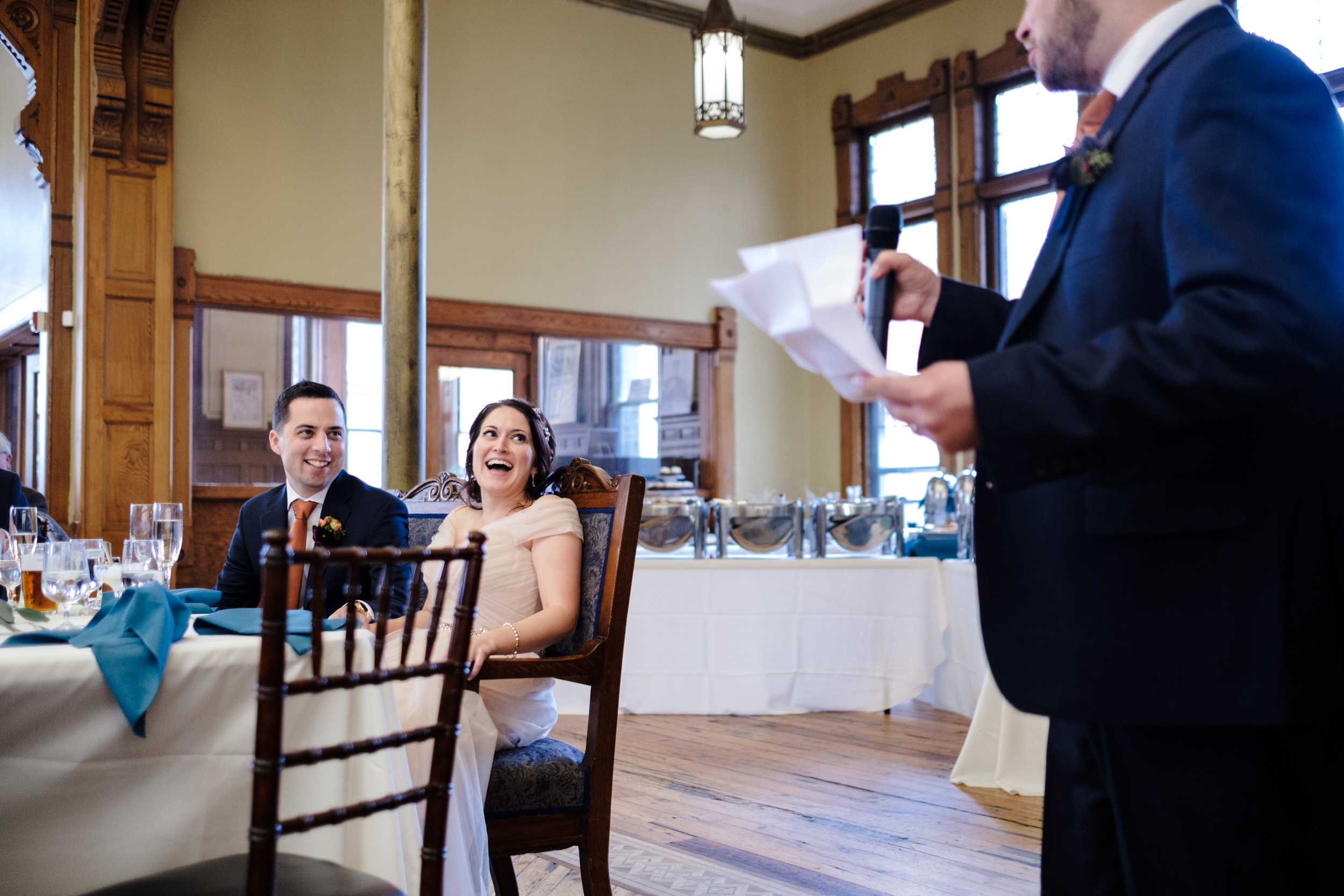 laughing candid wedding photo of couple at table during speech at pabst best place.