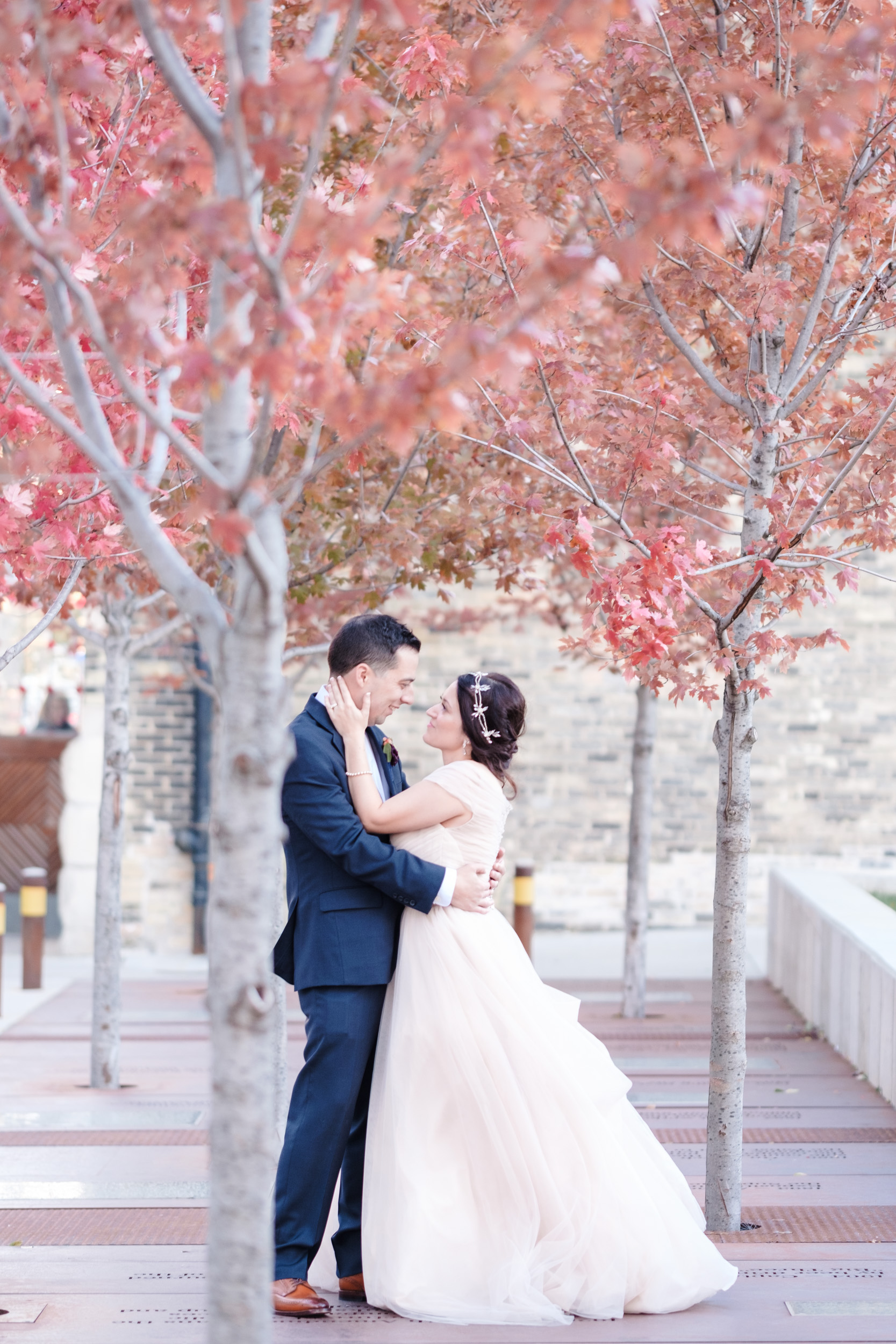 Artistic wedding portrait of bride and groom with red maple leaves behind in fall wedding.  Best Rockford wedding photographer.