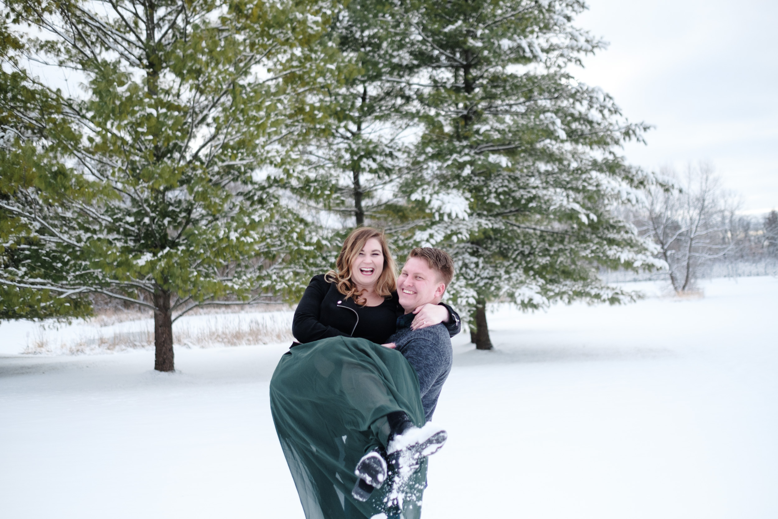 Groom carries his fiance in the snow at The Pavilion at Orchard Ridge Farms in Rockton, Illinois