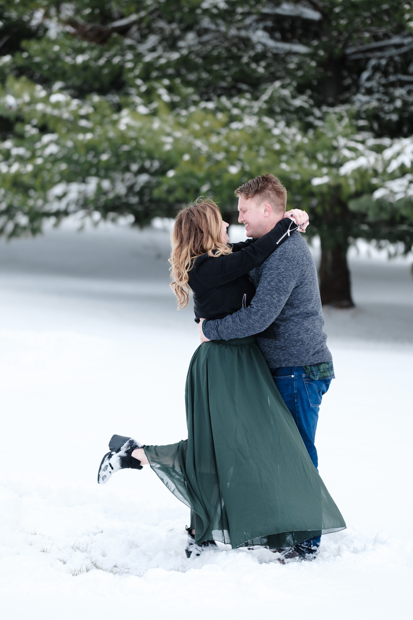 Engagement session of couple at Orchard Ridge Farms the Pavilion kissing in the snow by rockford wedding photographer B. adams photography