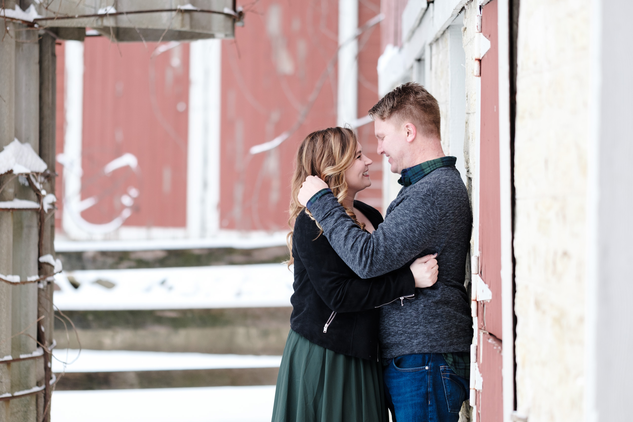 Engagement photo at orchard ridge farms the pavilion, couple leaning against the red barn and candidly embracing