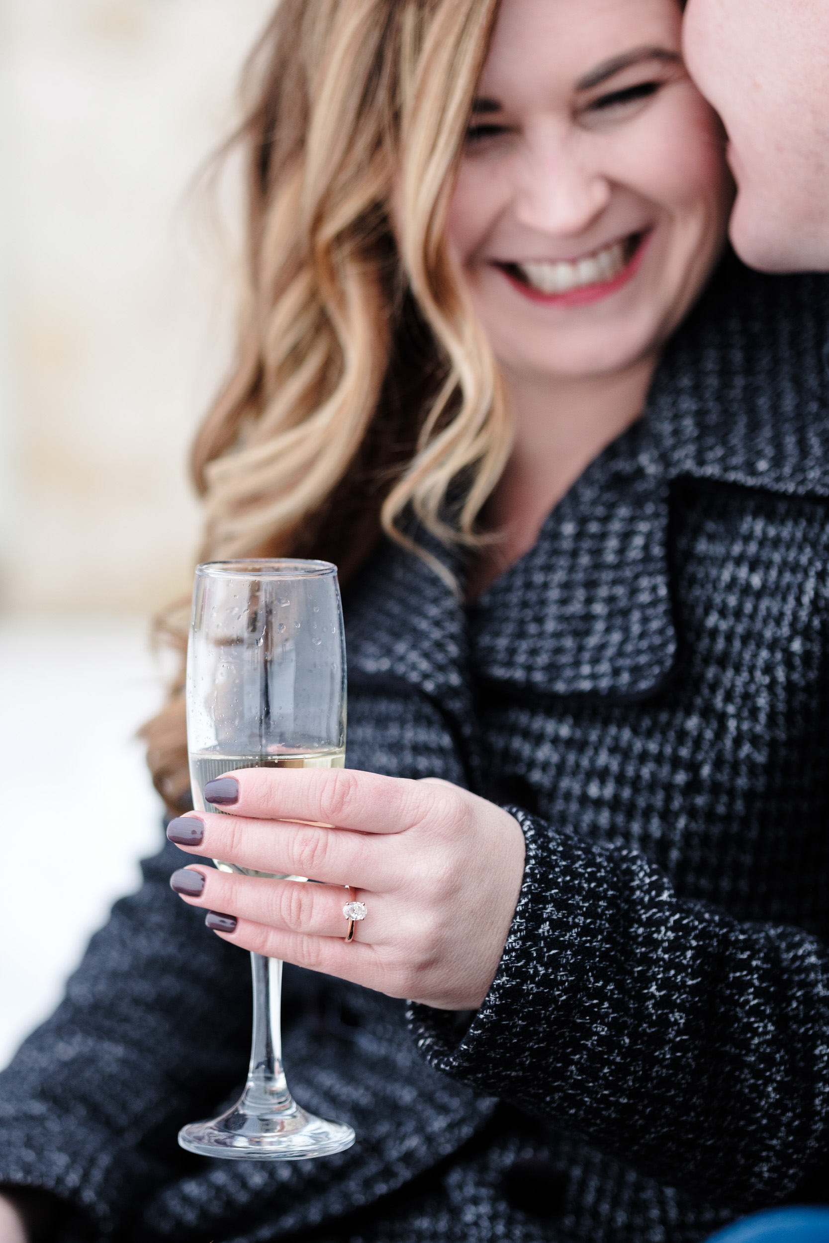 Engagement photo girl holding champagne glass with rose gold diamond engagement ring and nordstrom p coat at orchard ridge farms the pavilion