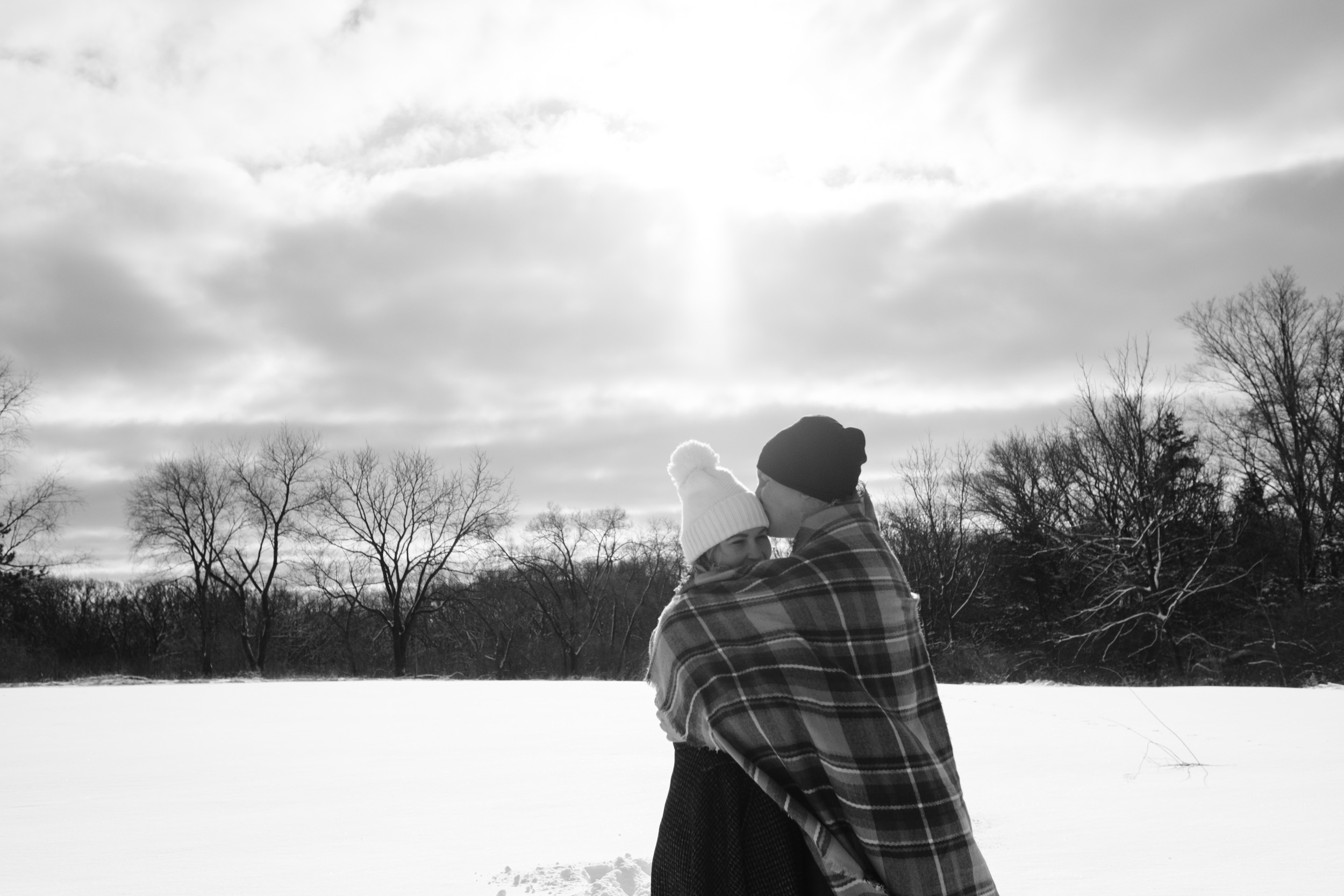 black and white engagement photo of couple snuggling under a buffalo check blanket while enjoying the sun during their winter wonderland engagement session