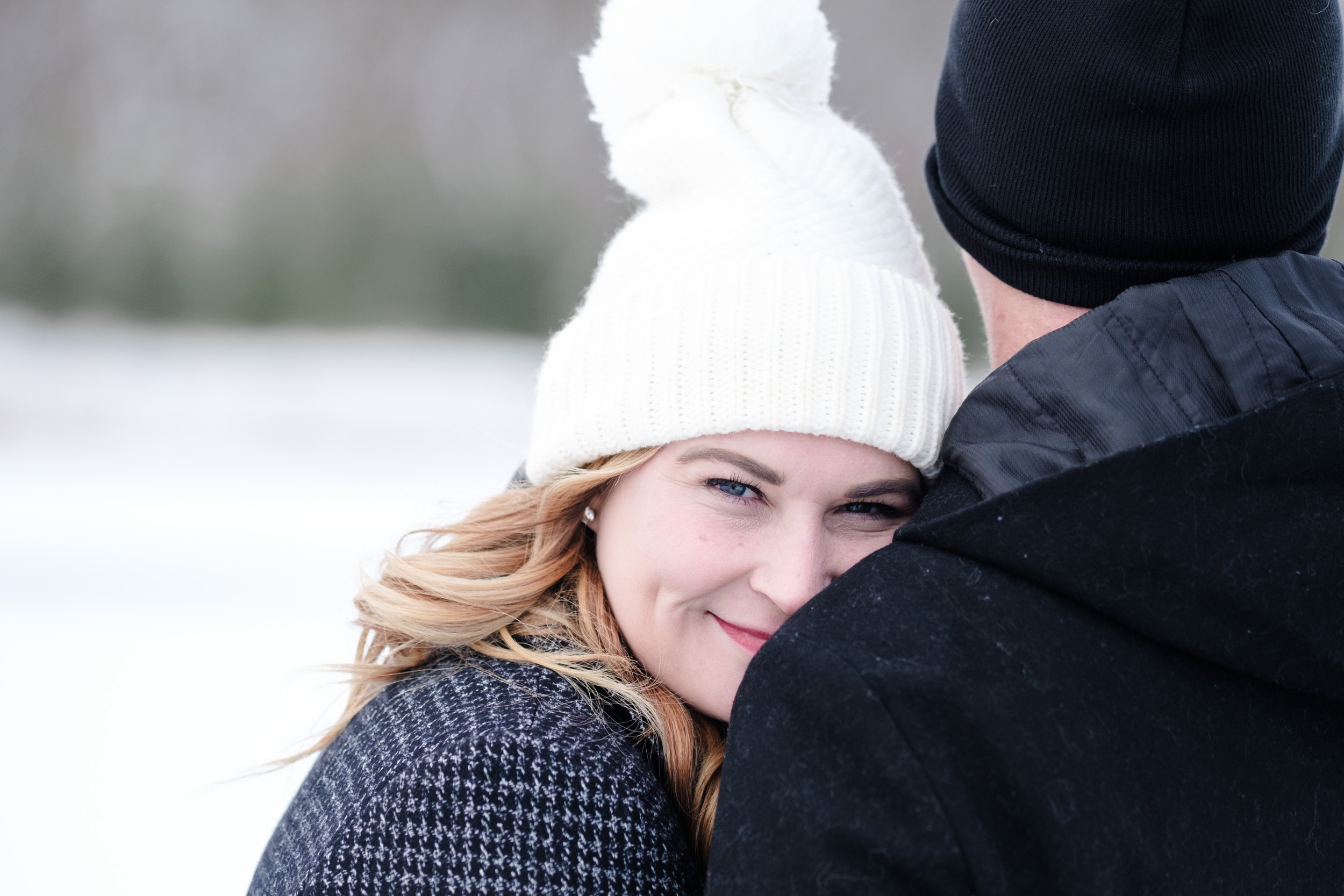 brides blue eyes as she looks back during engagement session in a winter wonderland at the pavilion at orchard ridge farms.