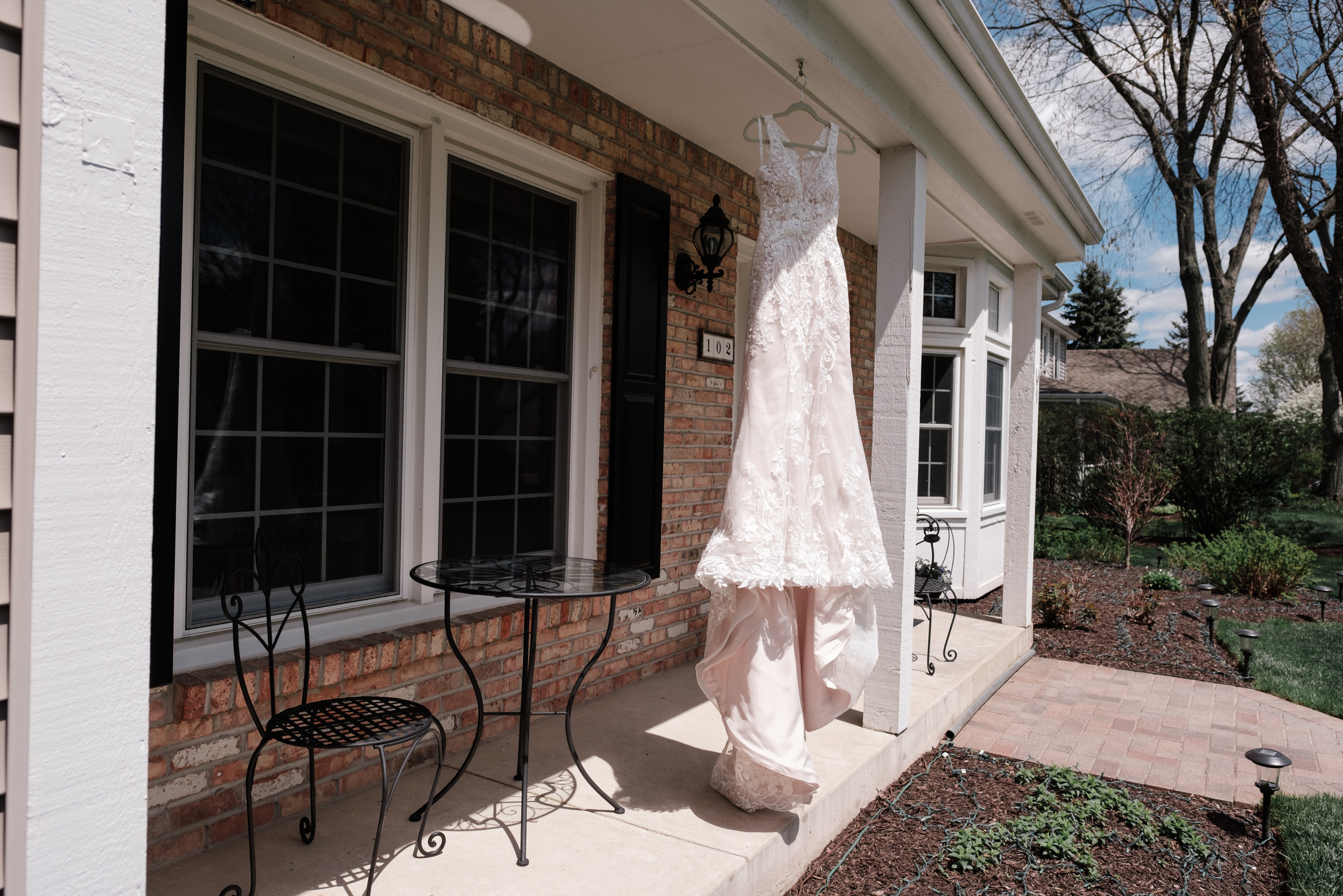 Bride dress hanging on front porch of childhood home in crystal lake