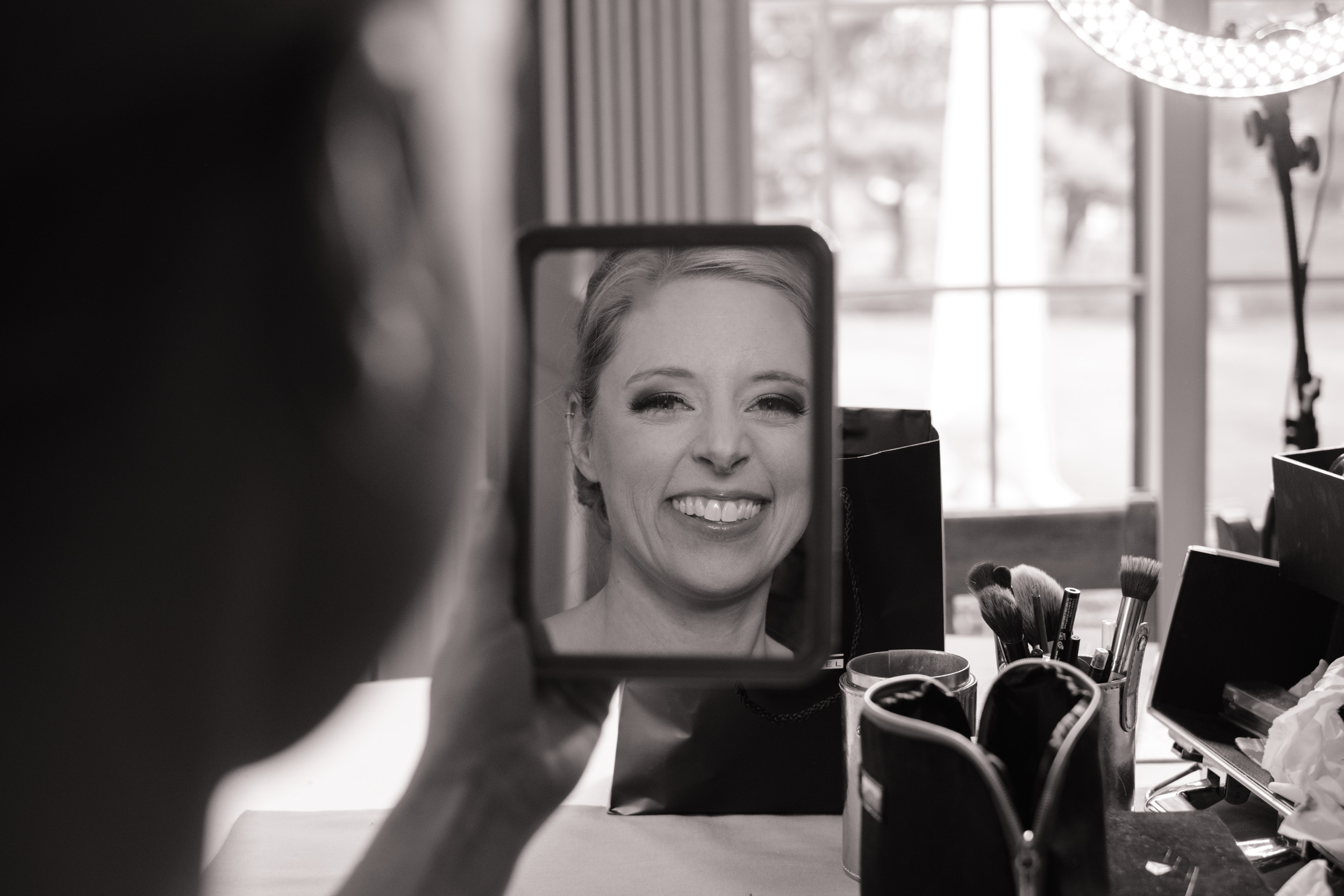 bride smiling in mirror looking at completed make on wedding day