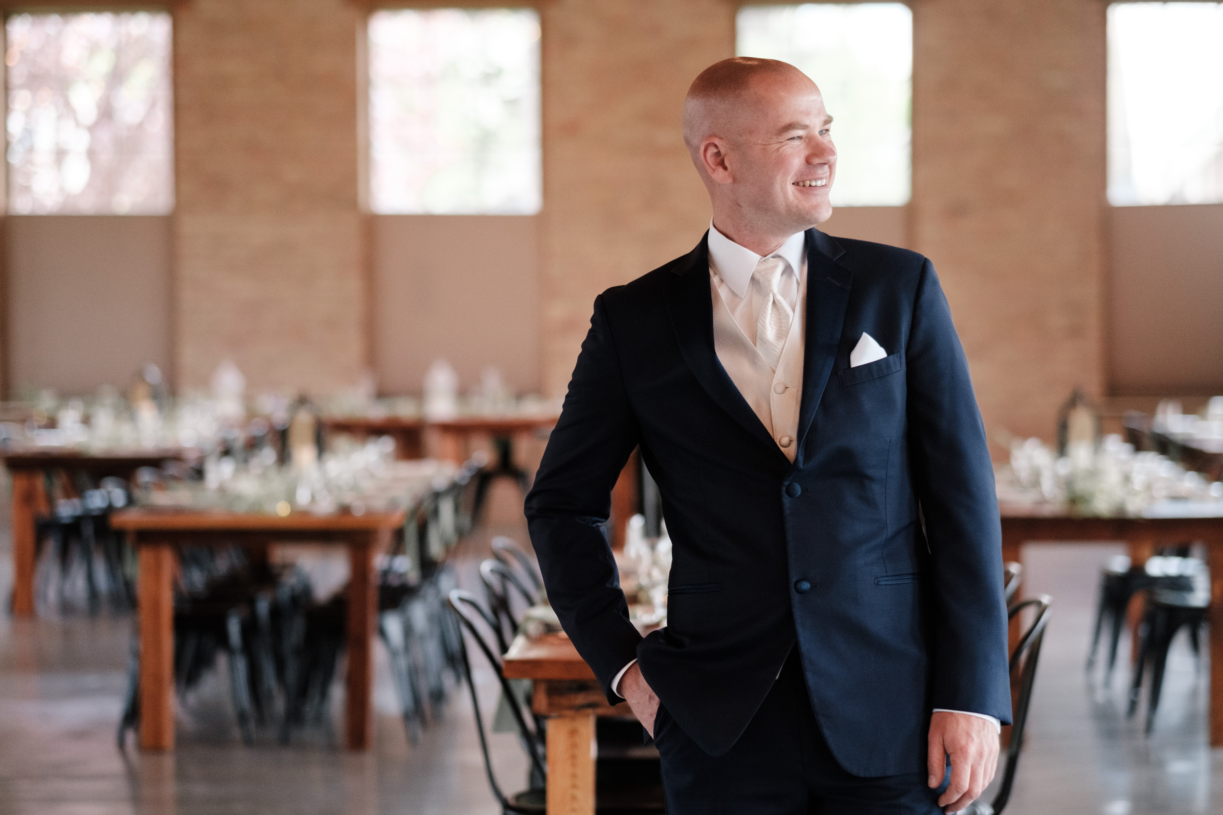 groom on wedding day pauses to look at venue, the brix