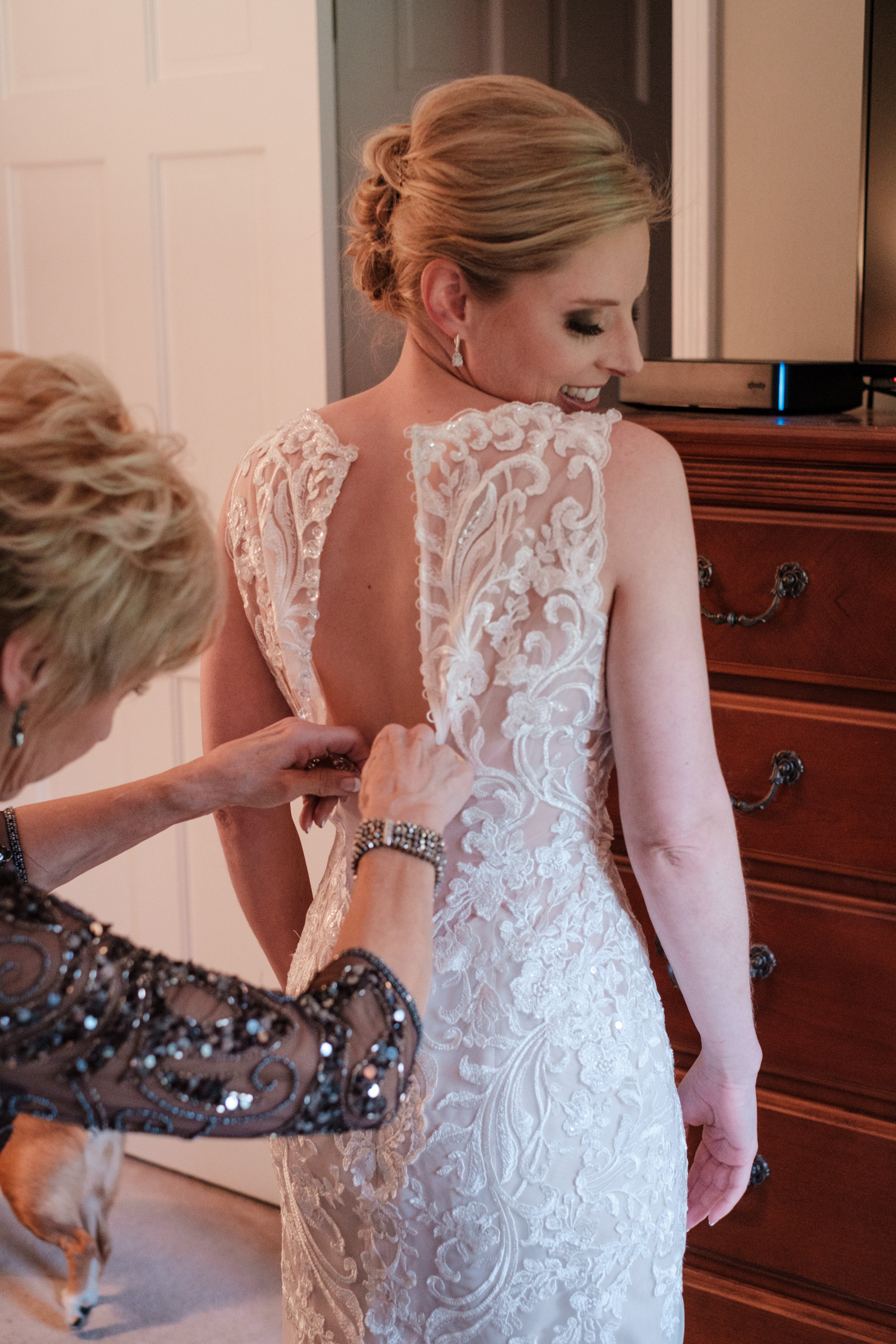 bride wedding day has dress buttoned up by mother
